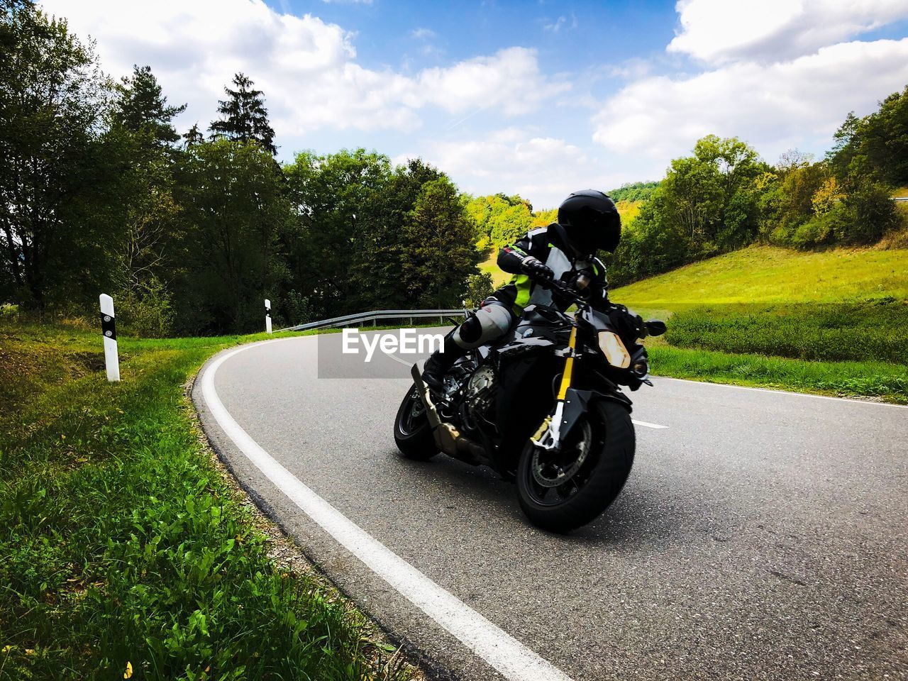 transportation, plant, tree, mode of transportation, motorcycle, sky, road, land vehicle, nature, helmet, cloud - sky, day, grass, real people, leisure activity, one person, full length, riding, outdoors, crash helmet