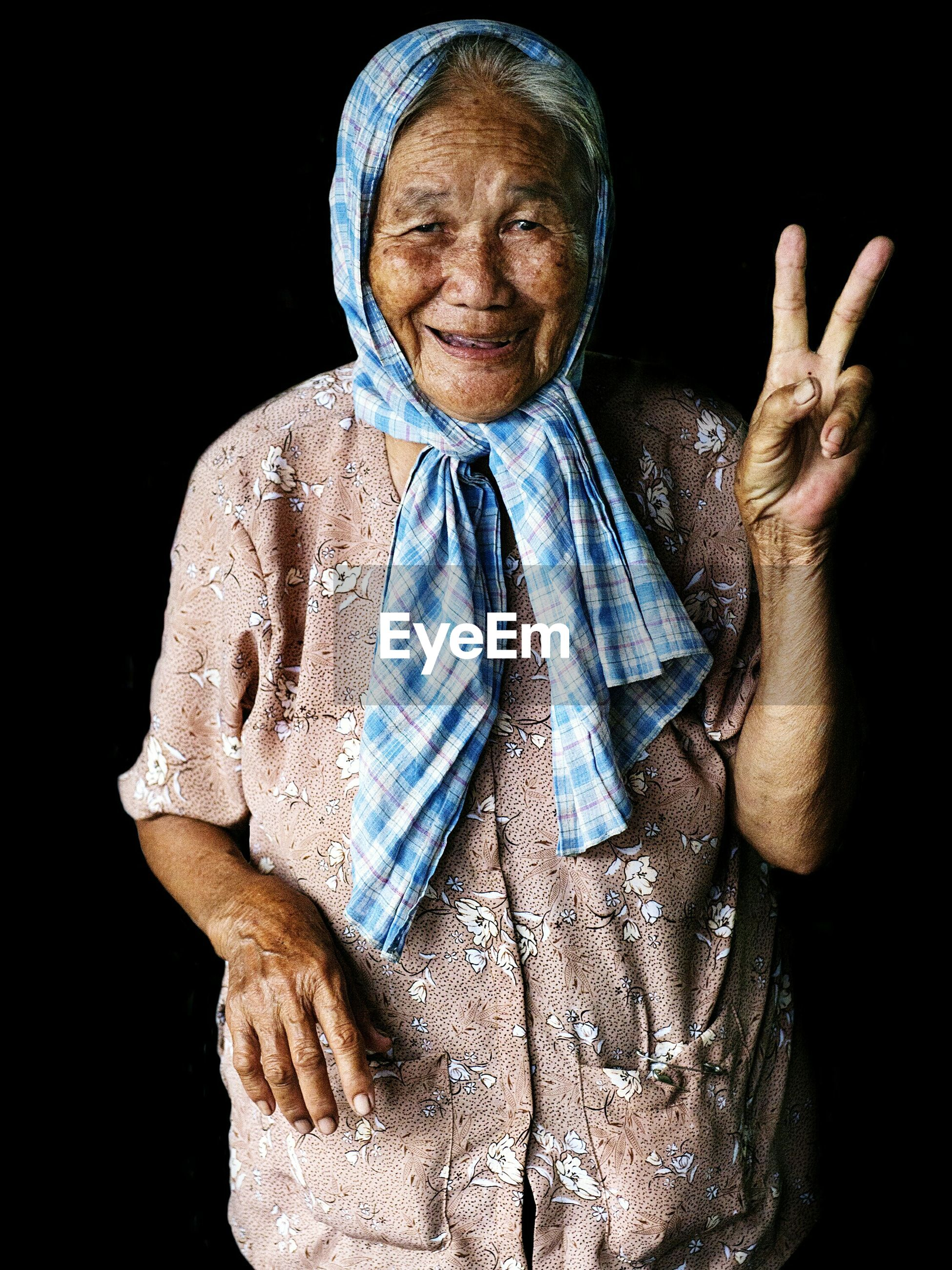 Portrait of smiling senior woman gesturing peace sign while standing against black background
