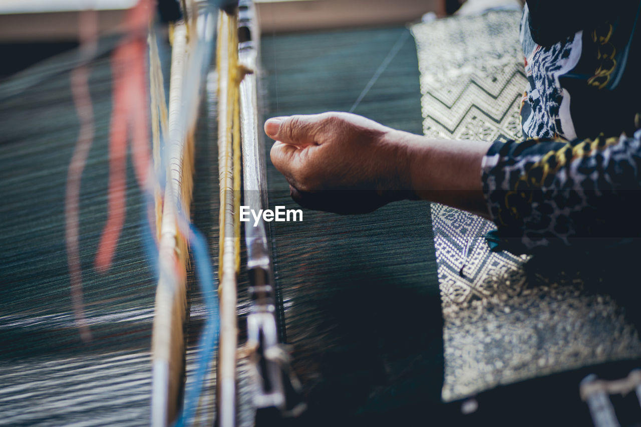 Midsection Of Woman Weaving Textile At Loom