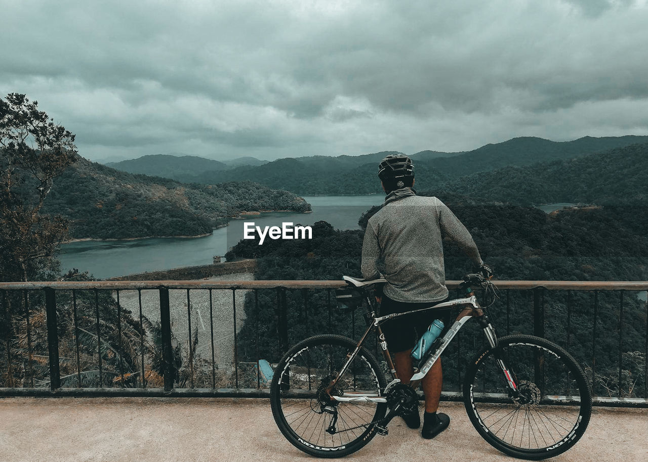 Rear view of man with bicycle standing by railing against sky