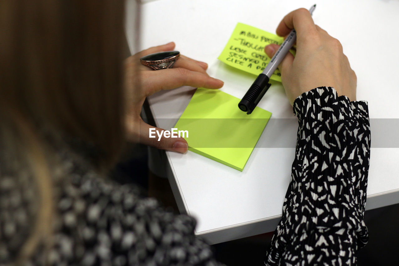 High angle view of woman writing on adhesive note at table