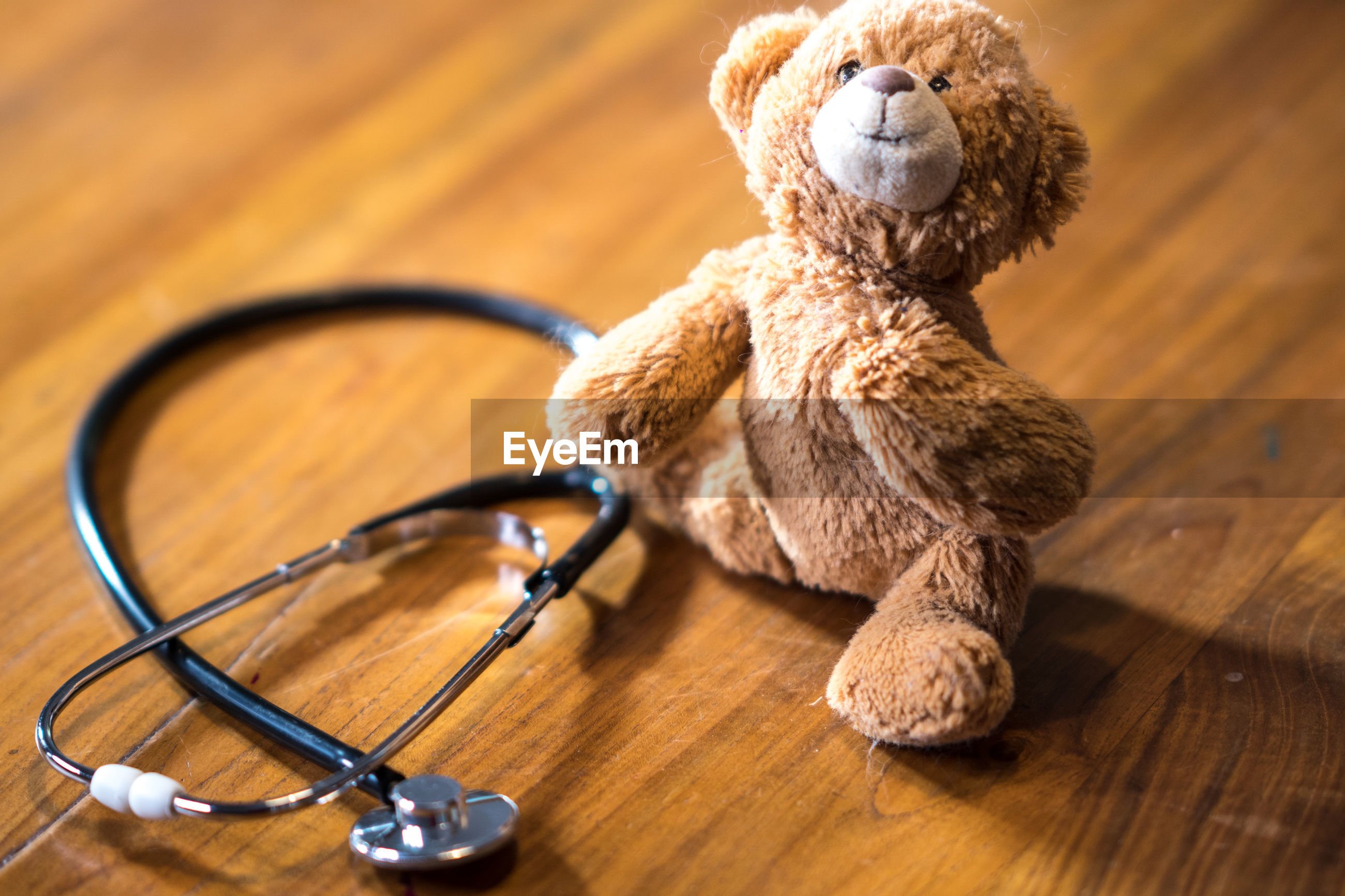 Pediatrics. stethoscope and stuffed toy bear on wooden table