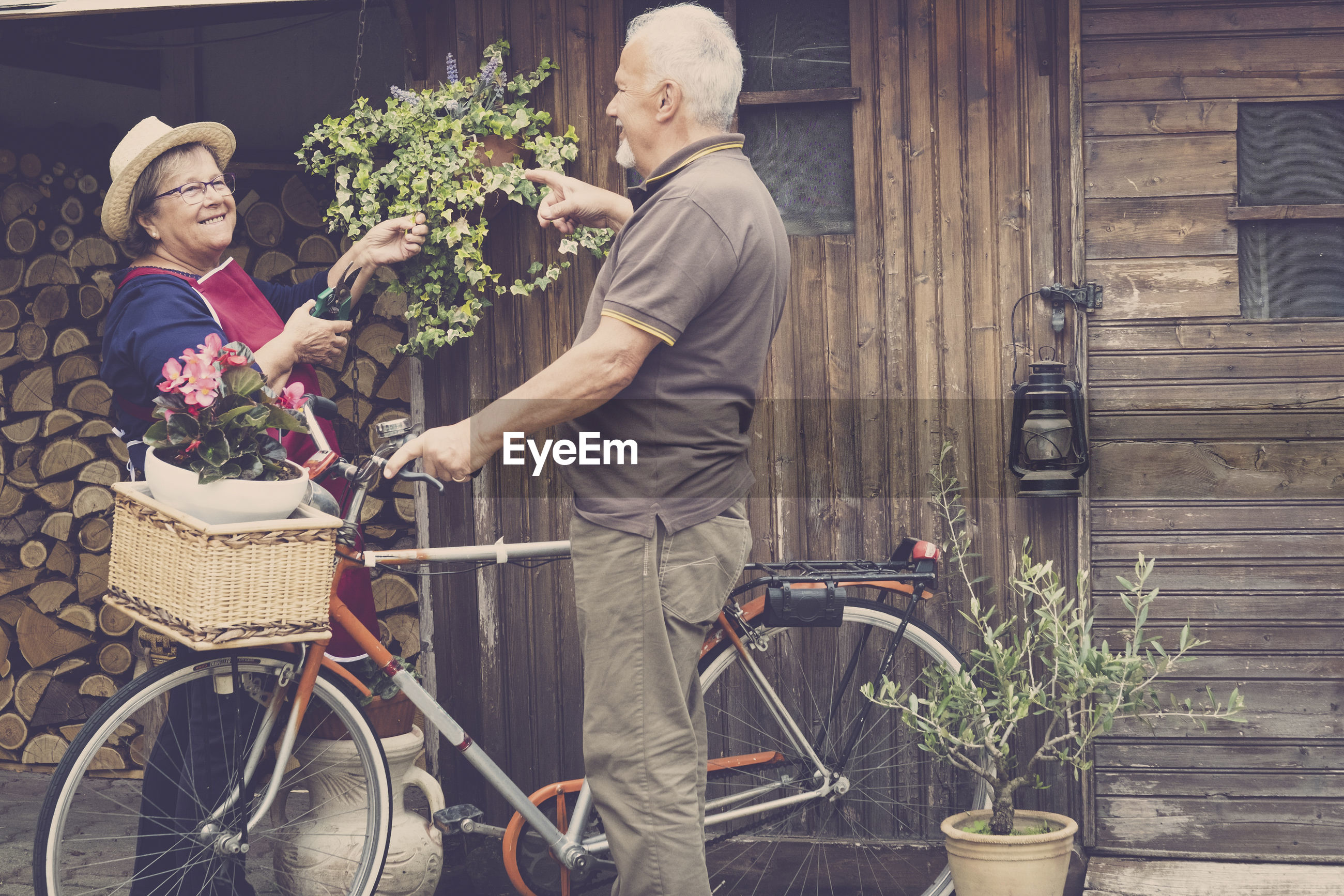 Senior couple standing with potted plant in bicycle basket against house