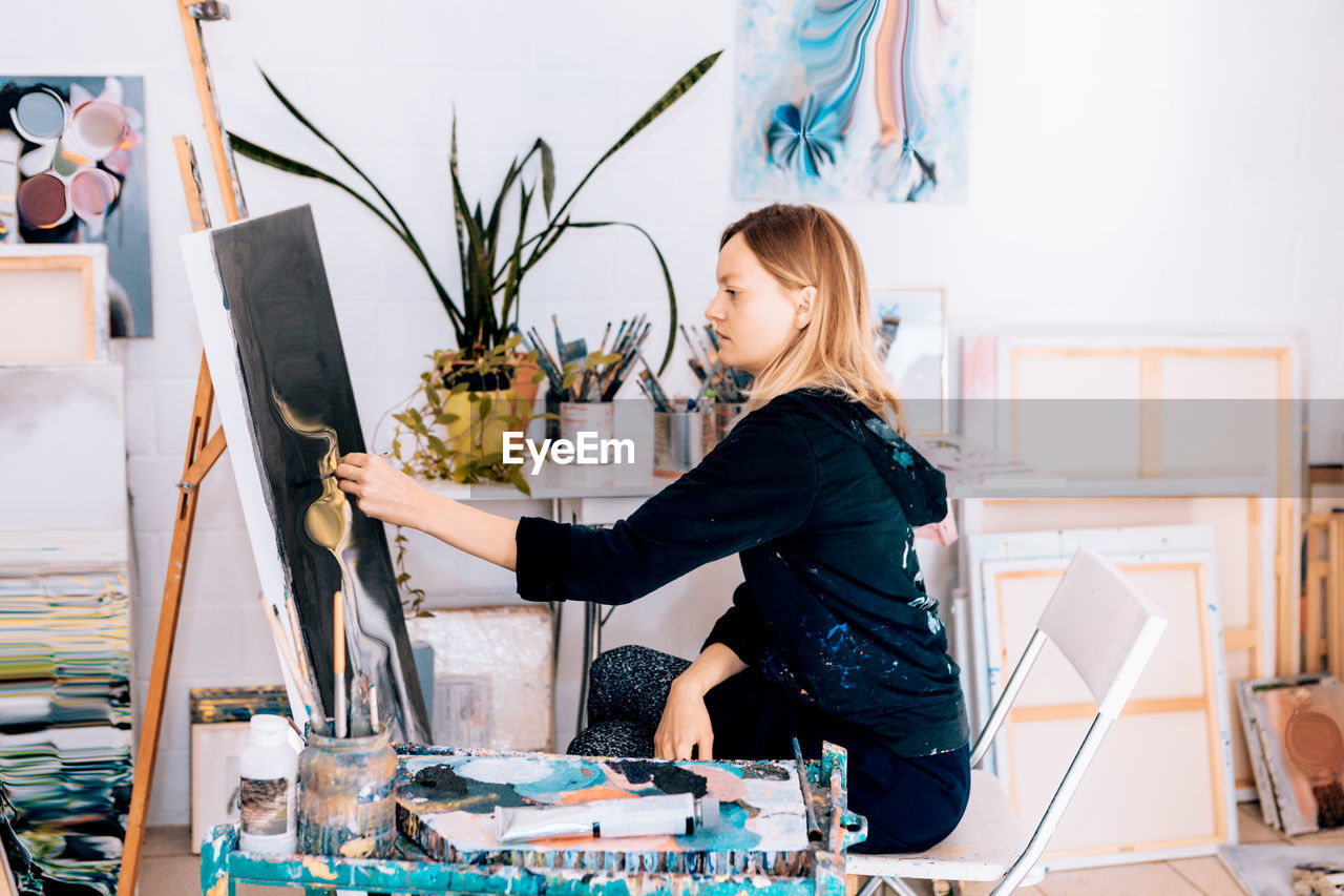 Side View Of Woman Painting At Studio