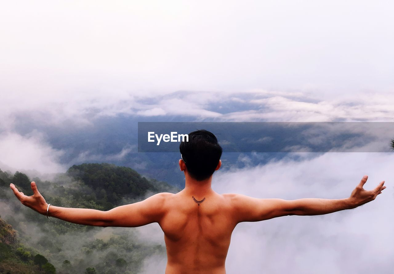 Rear view of shirtless man standing against sky