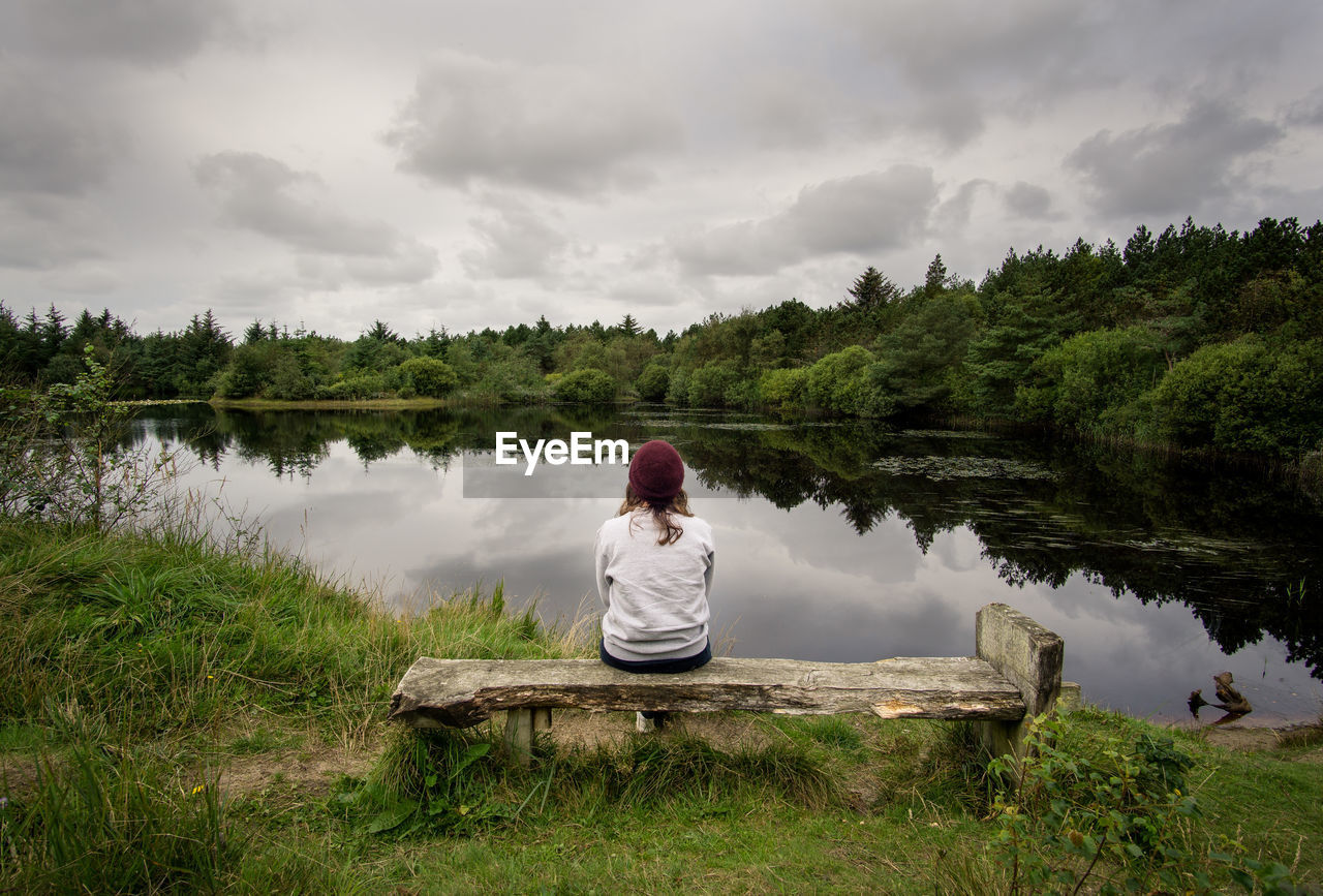 real people, water, lake, rear view, nature, beauty in nature, cloud - sky, sitting, one person, leisure activity, tree, full length, tranquility, sky, tranquil scene, lifestyles, growth, reflection, casual clothing, outdoors, day, scenics, women, young women, young adult