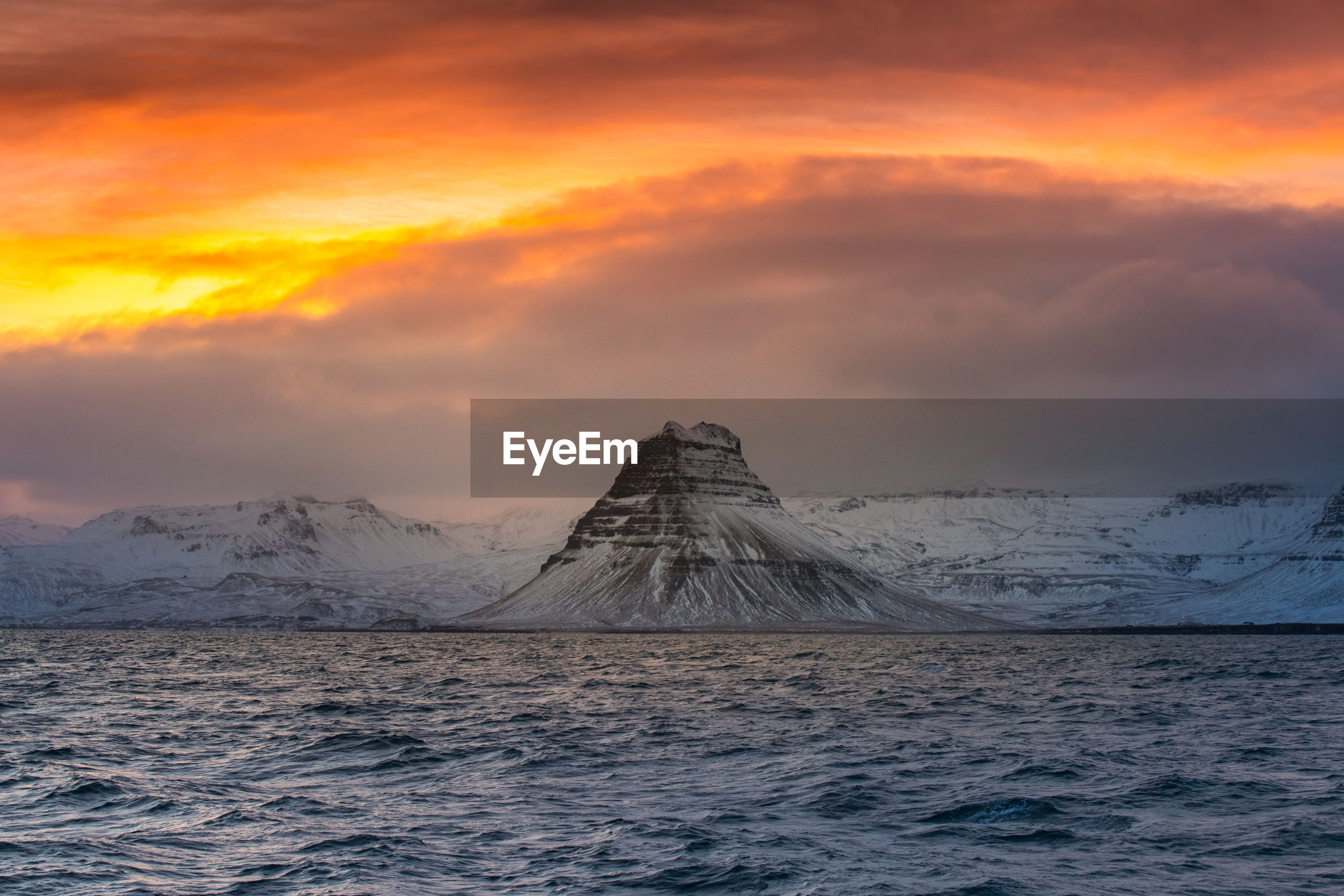 Scenic view of sea and snowcapped mountains against sky during sunset