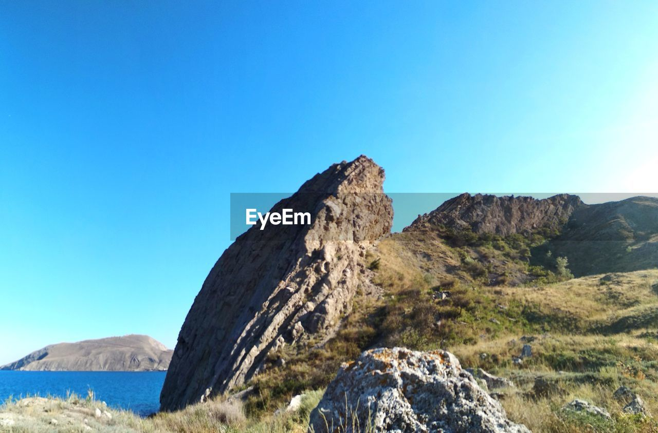 sky, mountain, beauty in nature, blue, tranquil scene, tranquility, clear sky, copy space, scenics - nature, nature, rock, no people, day, mountain range, non-urban scene, rock - object, solid, sunlight, idyllic, environment, outdoors, mountain peak, formation