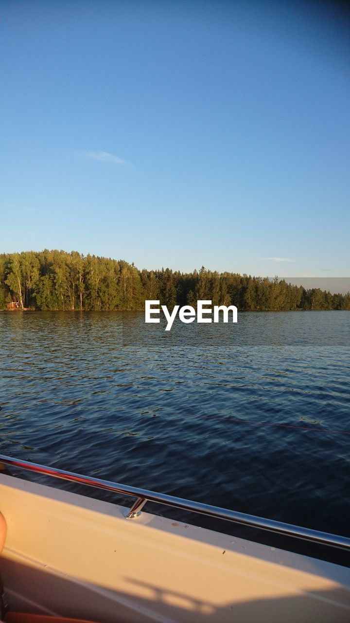 water, sky, mode of transportation, nautical vessel, transportation, lake, tree, scenics - nature, day, nature, plant, no people, tranquility, clear sky, beauty in nature, blue, tranquil scene, copy space, outdoors