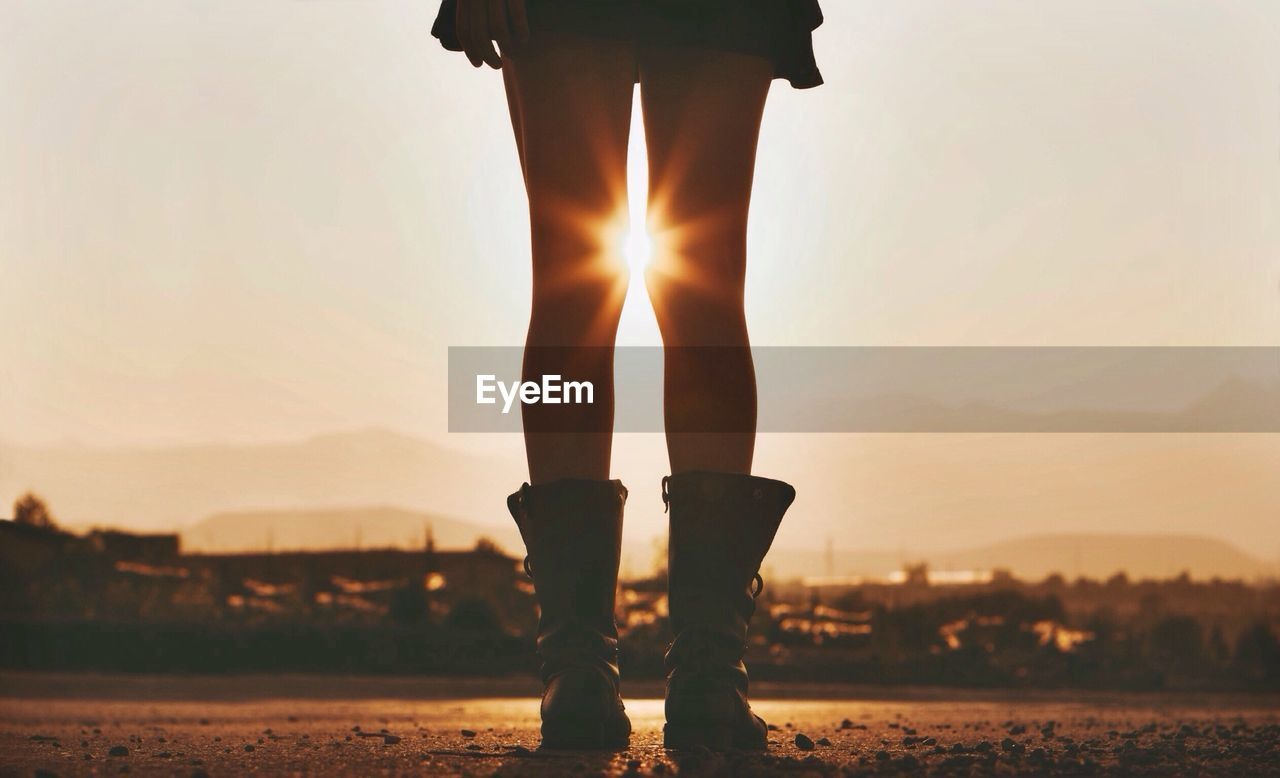 Low section of woman standing against sky during sunset