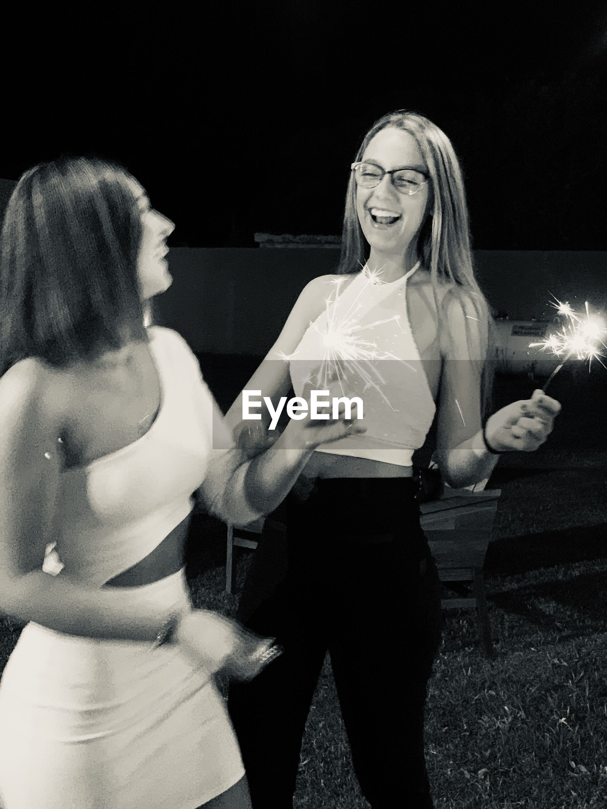 Smiling people holding illuminated sparklers while standing on land