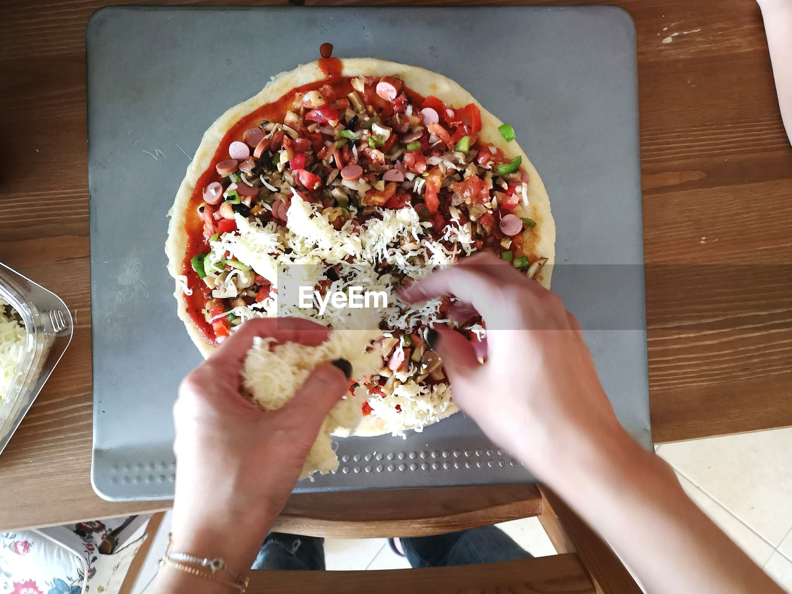 CROPPED IMAGE OF HAND HOLDING PIZZA