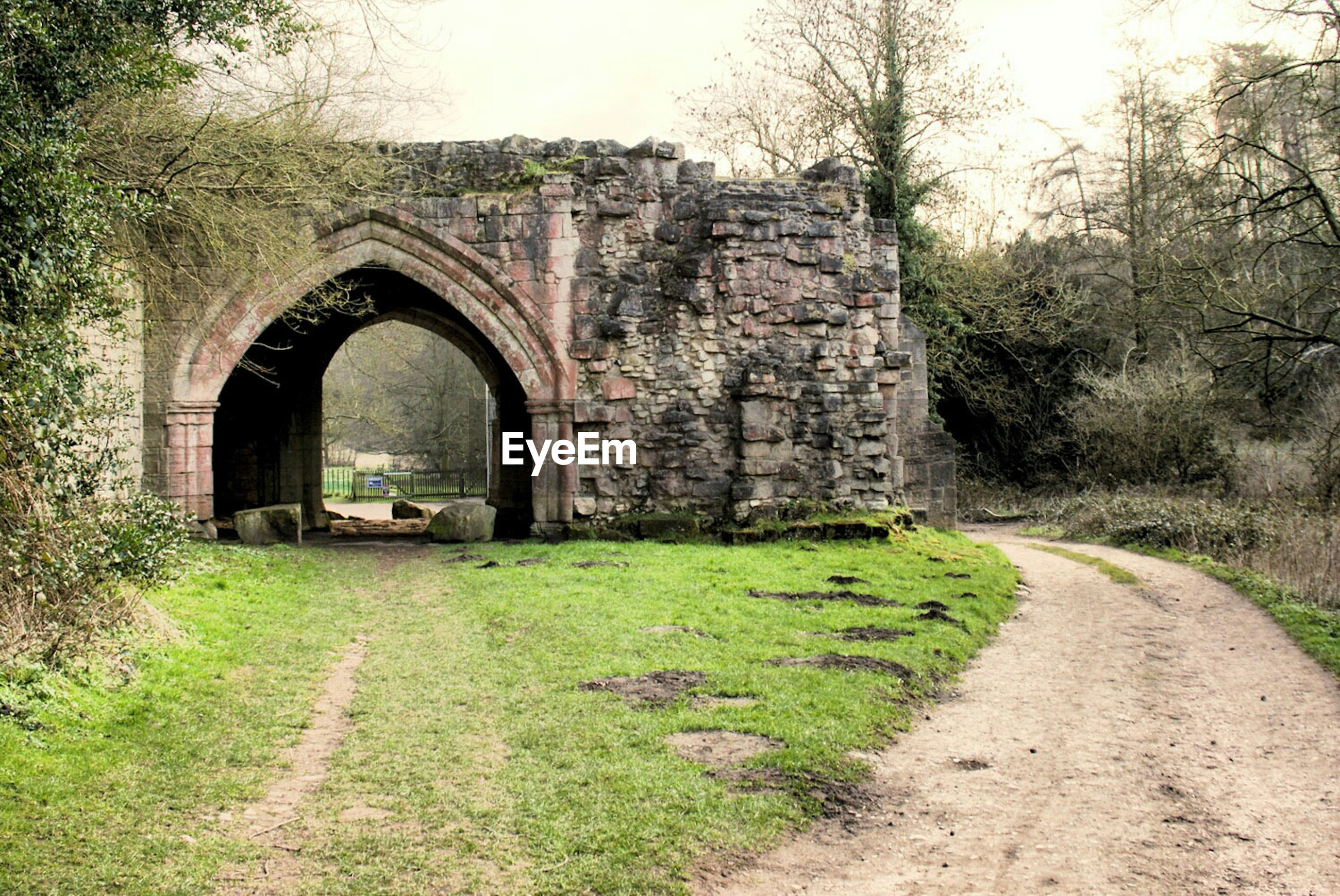 Empty road by old ruin arch gate