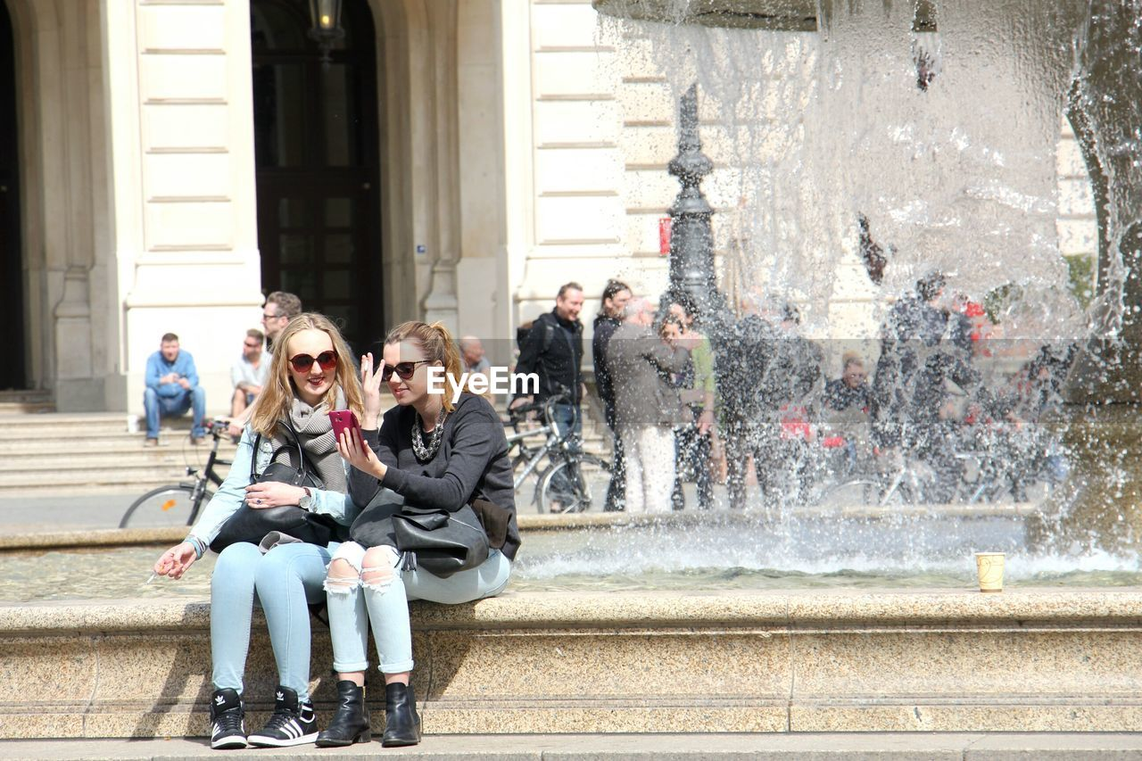 togetherness, city, day, sitting, casual clothing, young women, young adult, outdoors, men, happiness, full length, building exterior, women, architecture, real people, adult, people, friendship, student, adults only