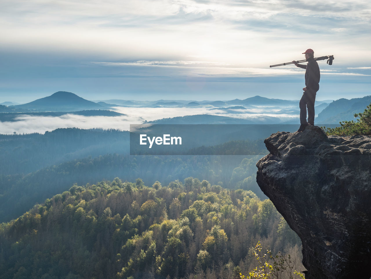 Nature photographer carry camera with tripod on his shoulder and look from mountain cliff to mist