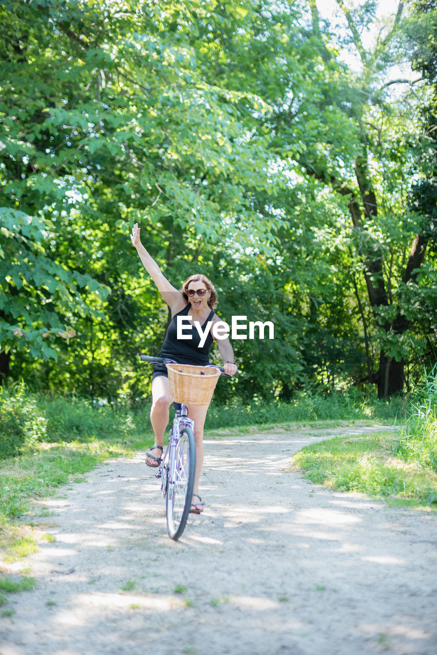 Happy woman riding bicycle on road