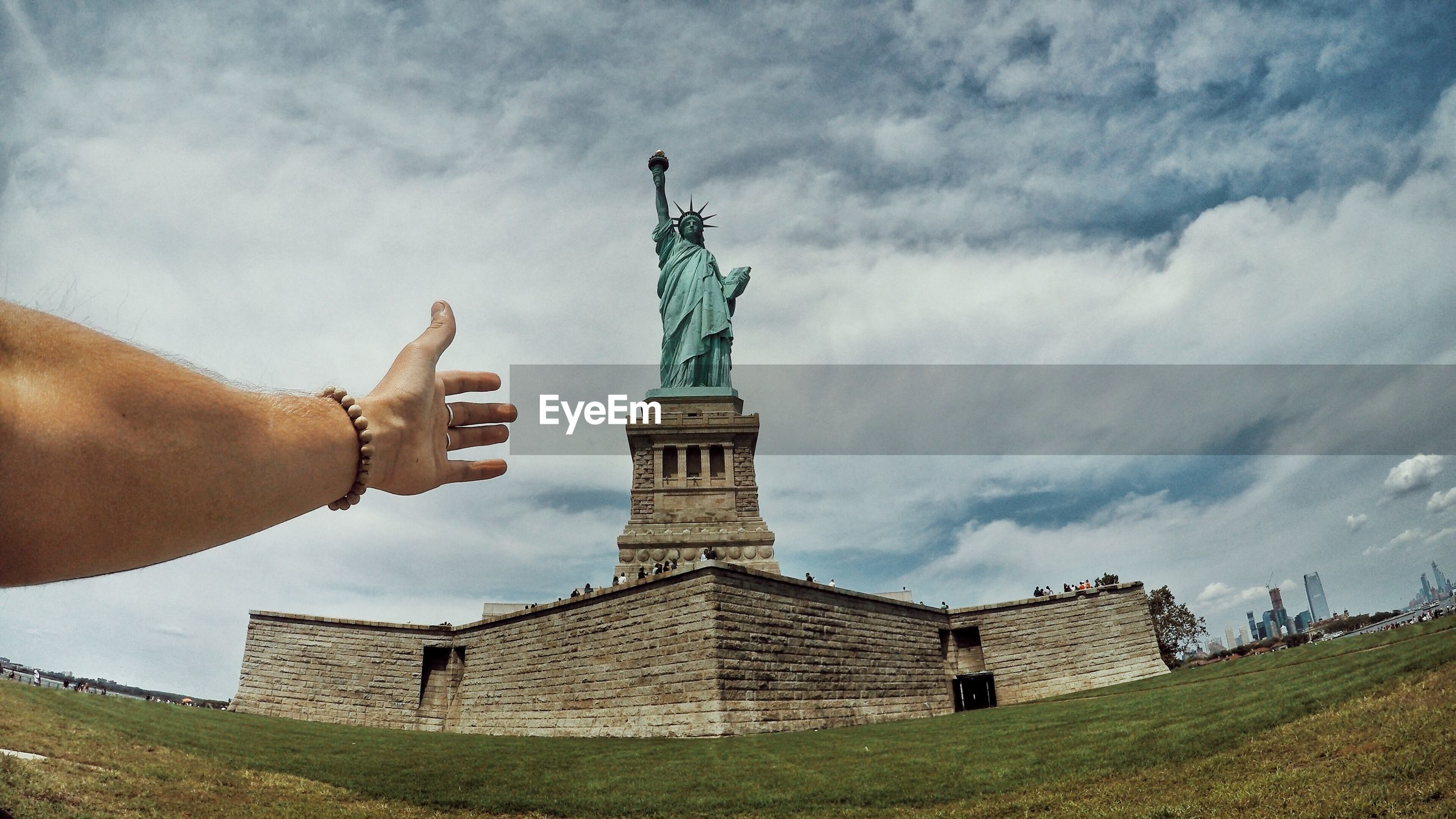 Low angle view of hand gesturing with statue of liberty in background against cloudy sky