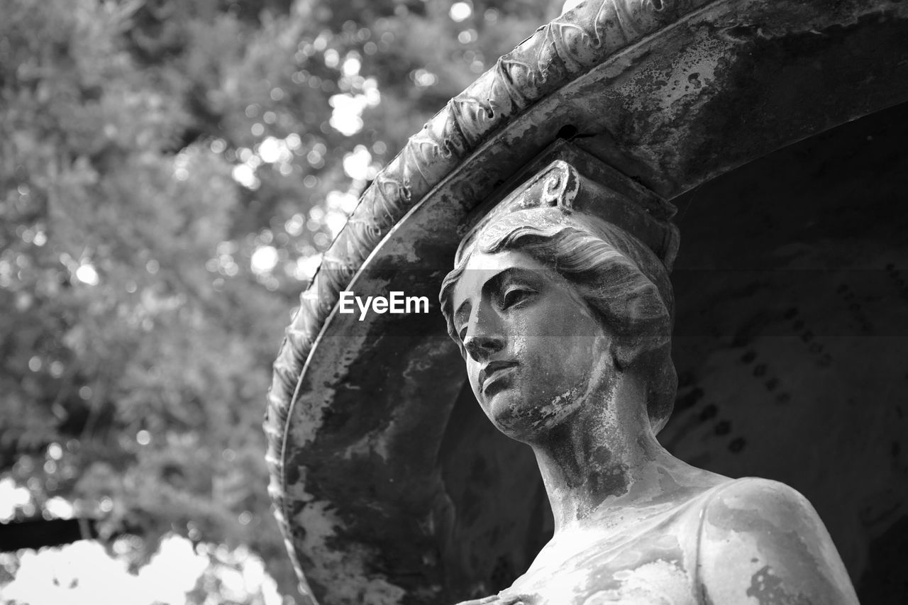 Low Angle View Of Old Sculpture At Cemetery