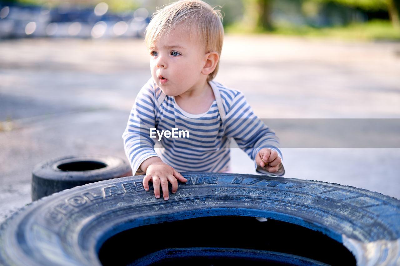 PORTRAIT OF CUTE BABY BOY LOOKING THROUGH CAMERA