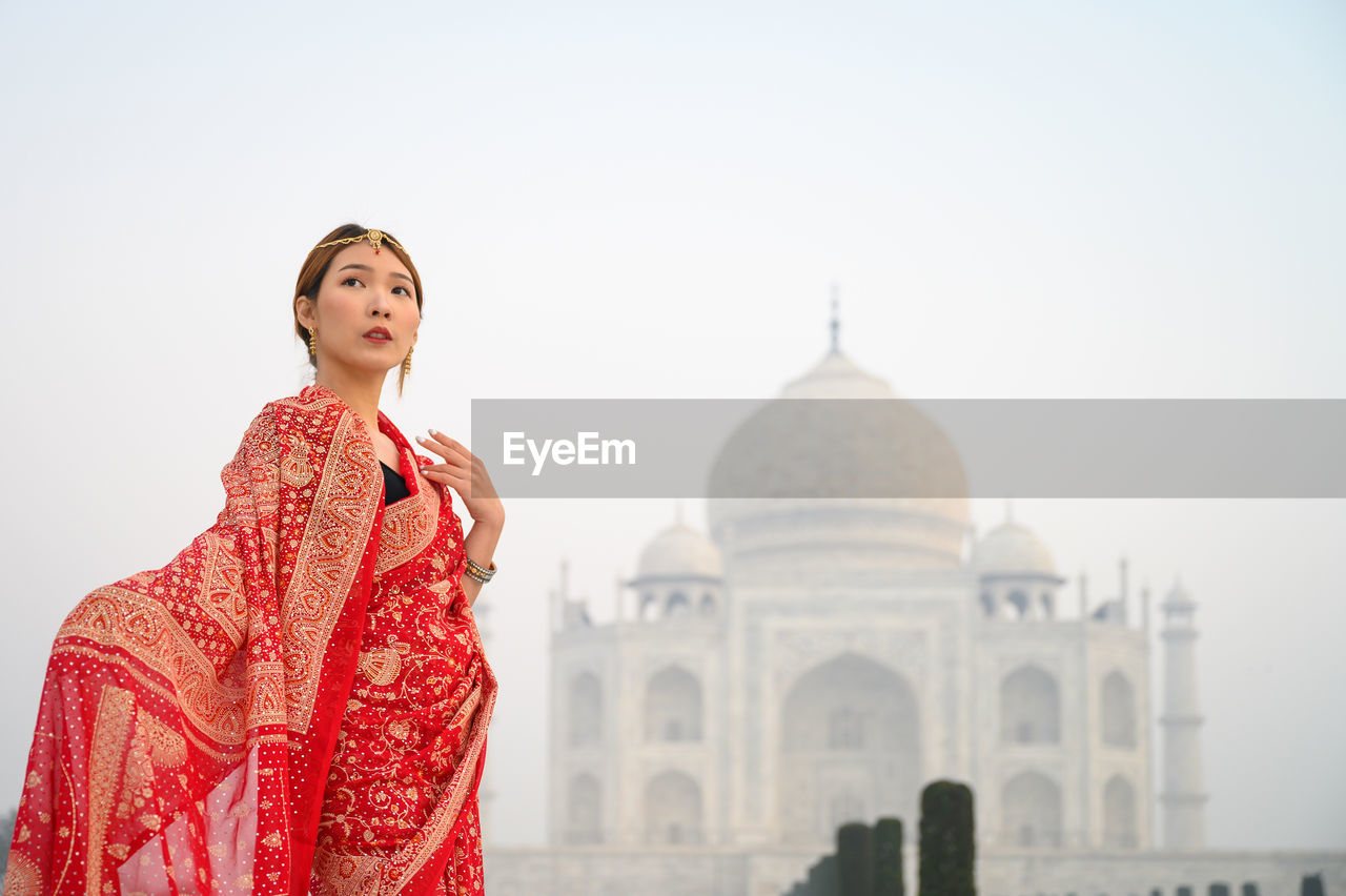 Young woman standing against historic building in india