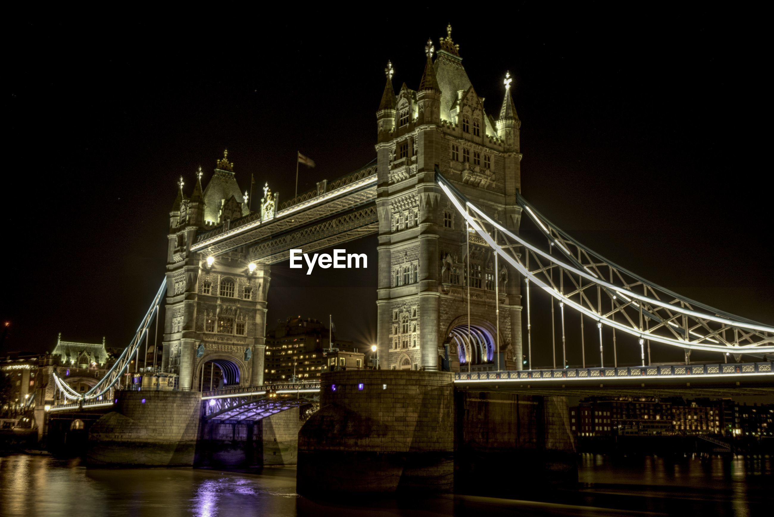 Illuminated tower bridge over river against at night