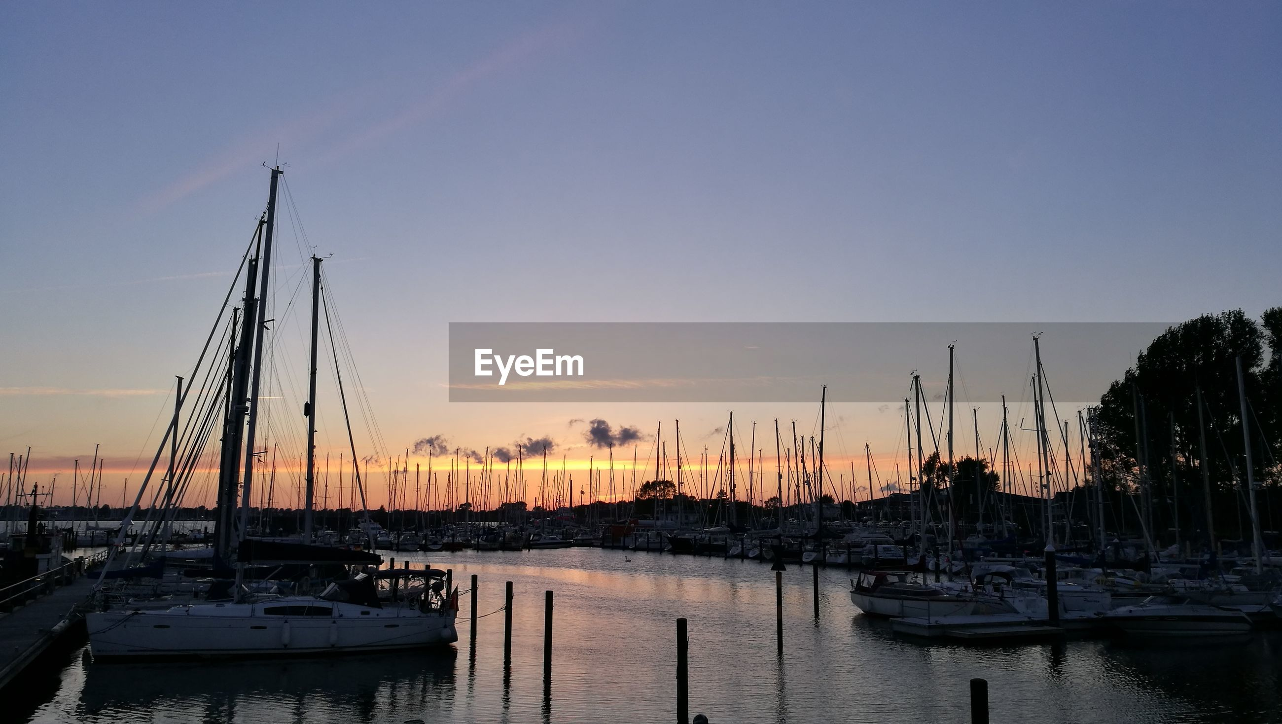 SAILBOATS MOORED IN HARBOR DURING SUNSET