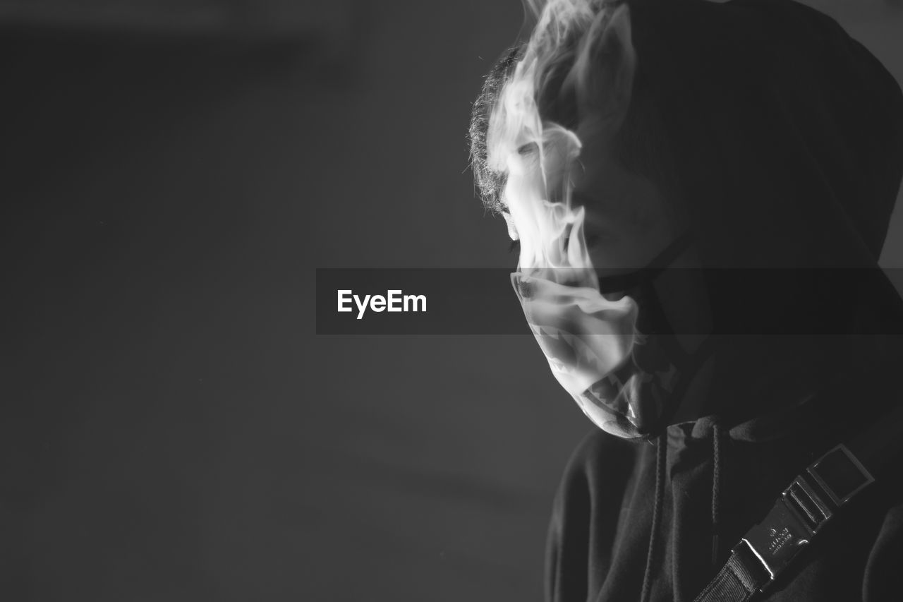 Close-Up Of Man Wearing Mask While Smoking Against Wall
