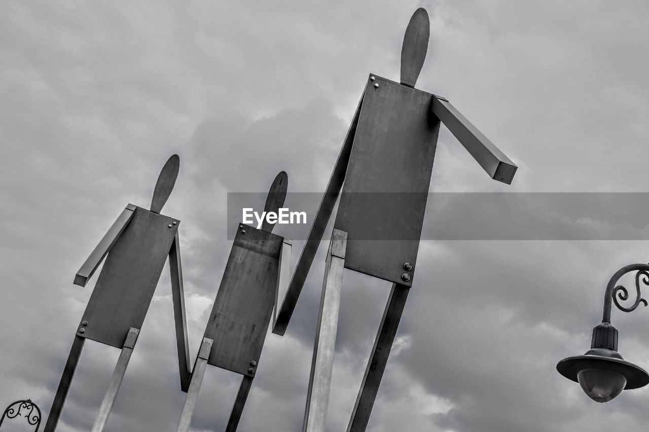 cloud - sky, sky, low angle view, nature, no people, day, metal, in a row, outdoors, pole, sign, communication, technology, protection, tall - high, panoramic, side by side, choice, security
