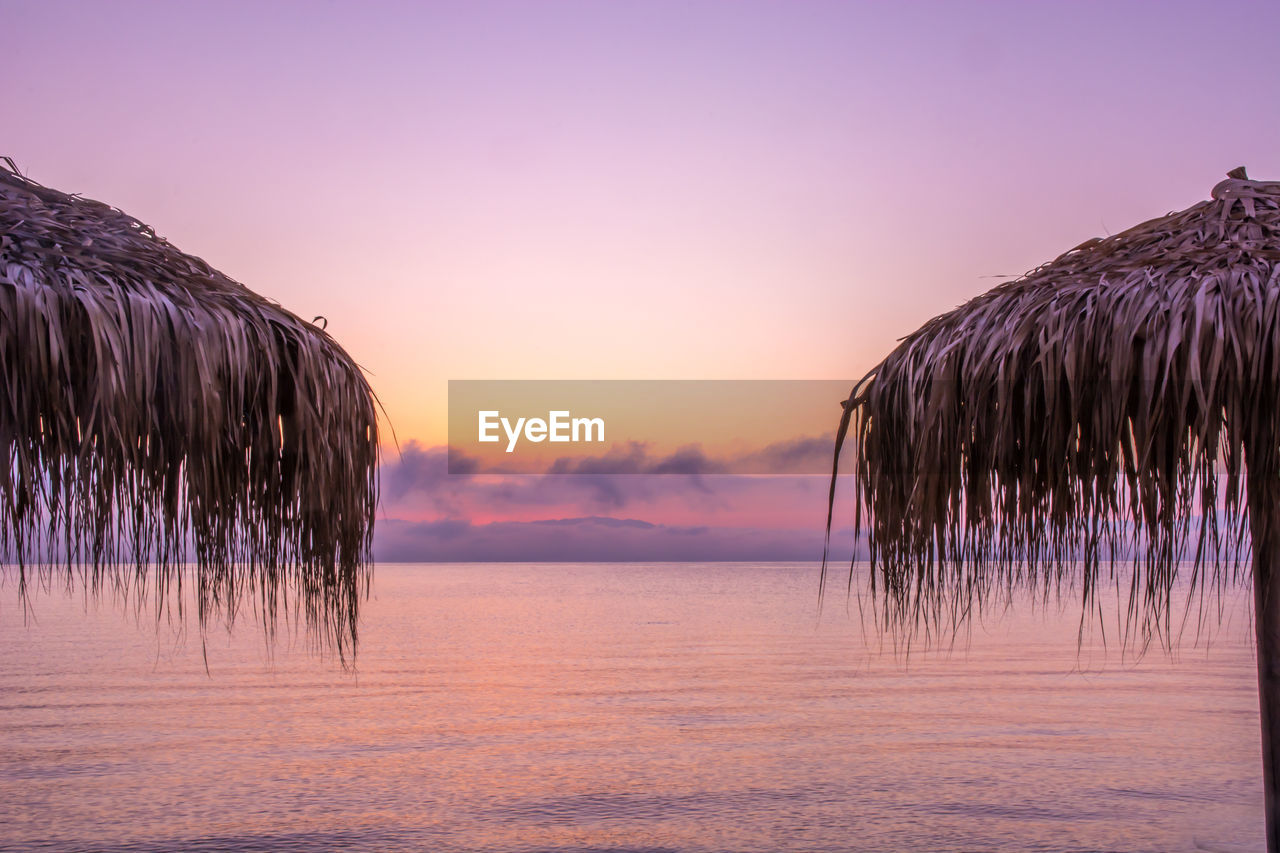 sky, sunset, tranquility, water, scenics - nature, beauty in nature, no people, nature, tranquil scene, sea, thatched roof, land, idyllic, beach, orange color, roof, waterfront, outdoors, dusk