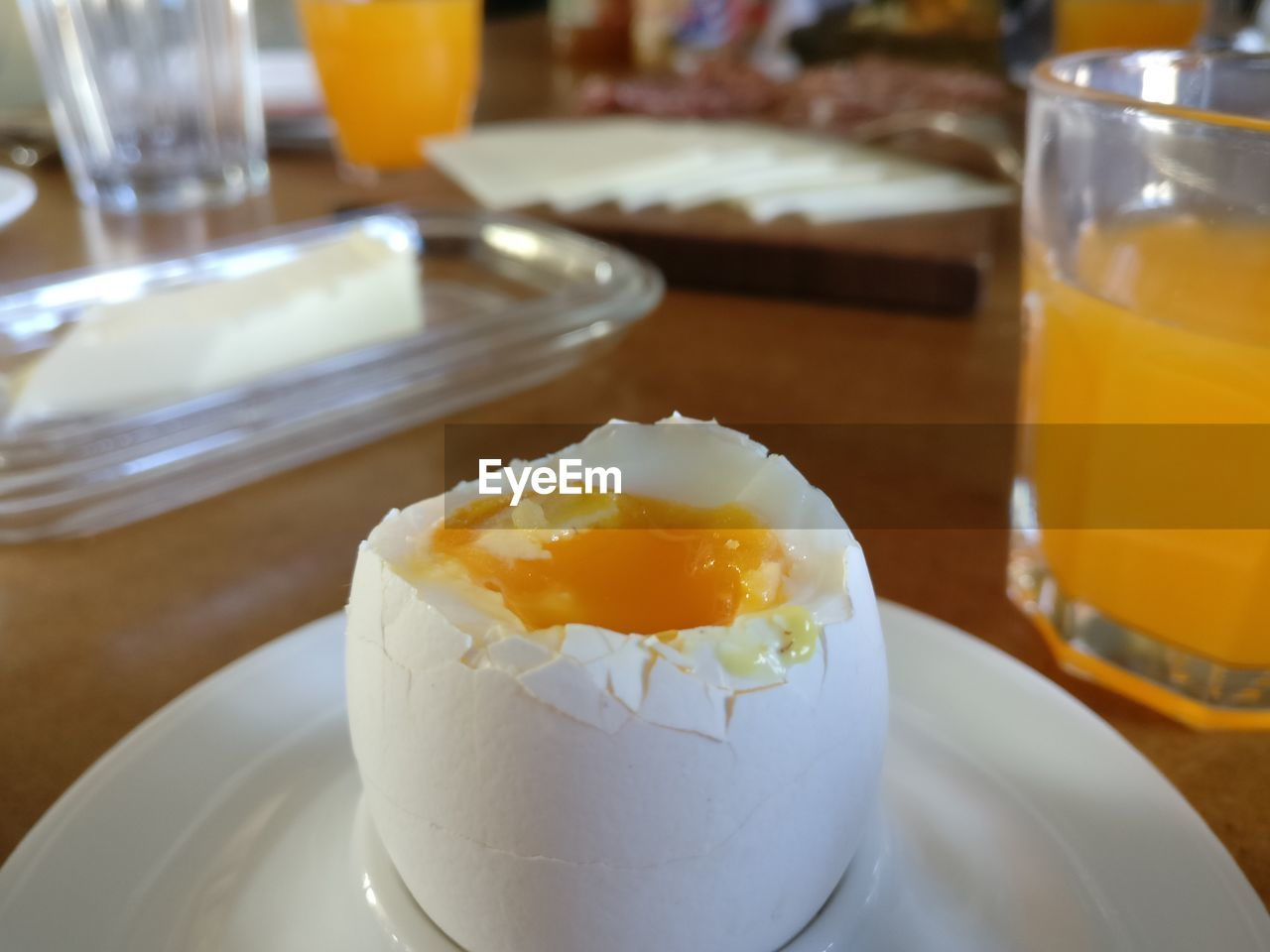 Close-Up Of Tasty Breakfast Egg And Healthy Orange Juice On Table