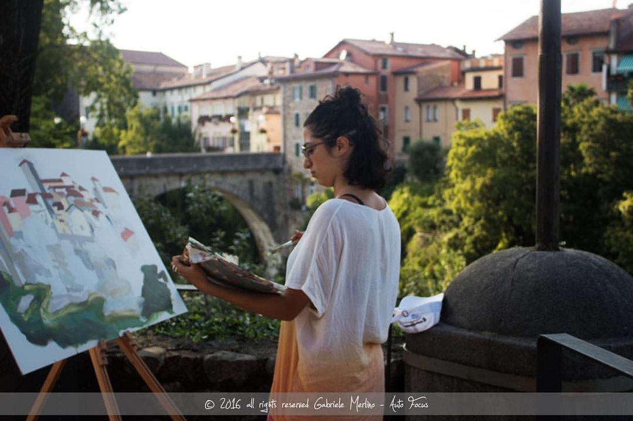 artist, real people, easel, one person, leisure activity, standing, women, outdoors, day, architecture, young adult, adult, people