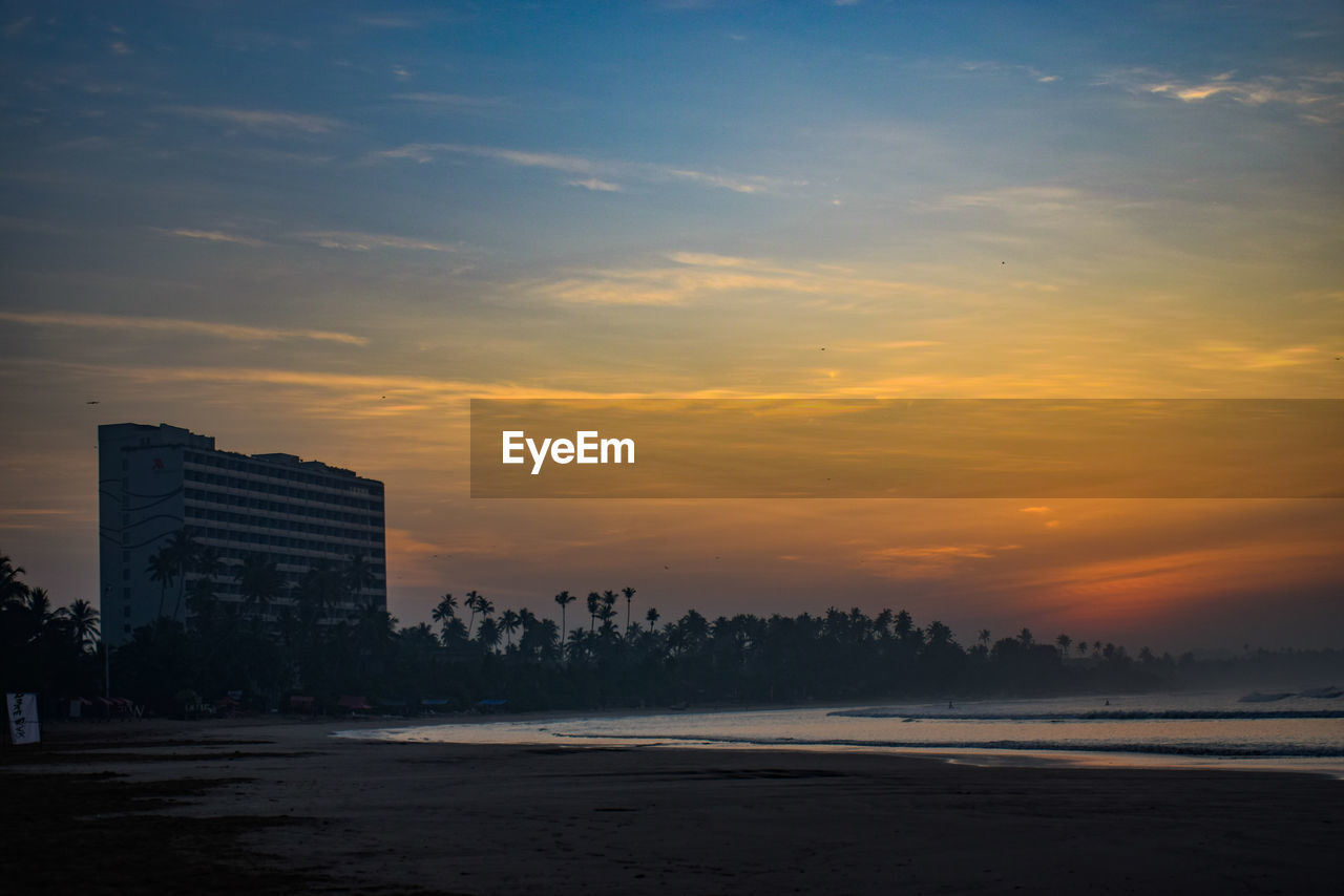 sunset, architecture, skyscraper, sky, city, built structure, building exterior, beach, outdoors, cityscape, no people, sea, modern, nature