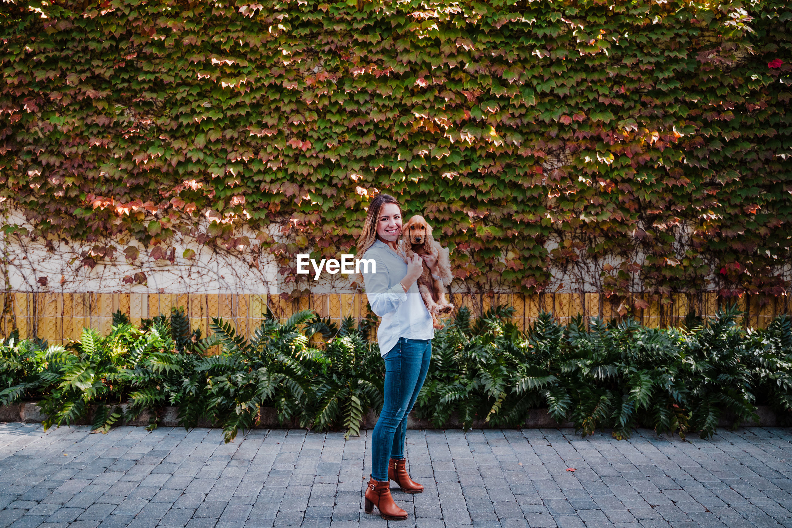 Full length portrait of smiling young woman standing against plants