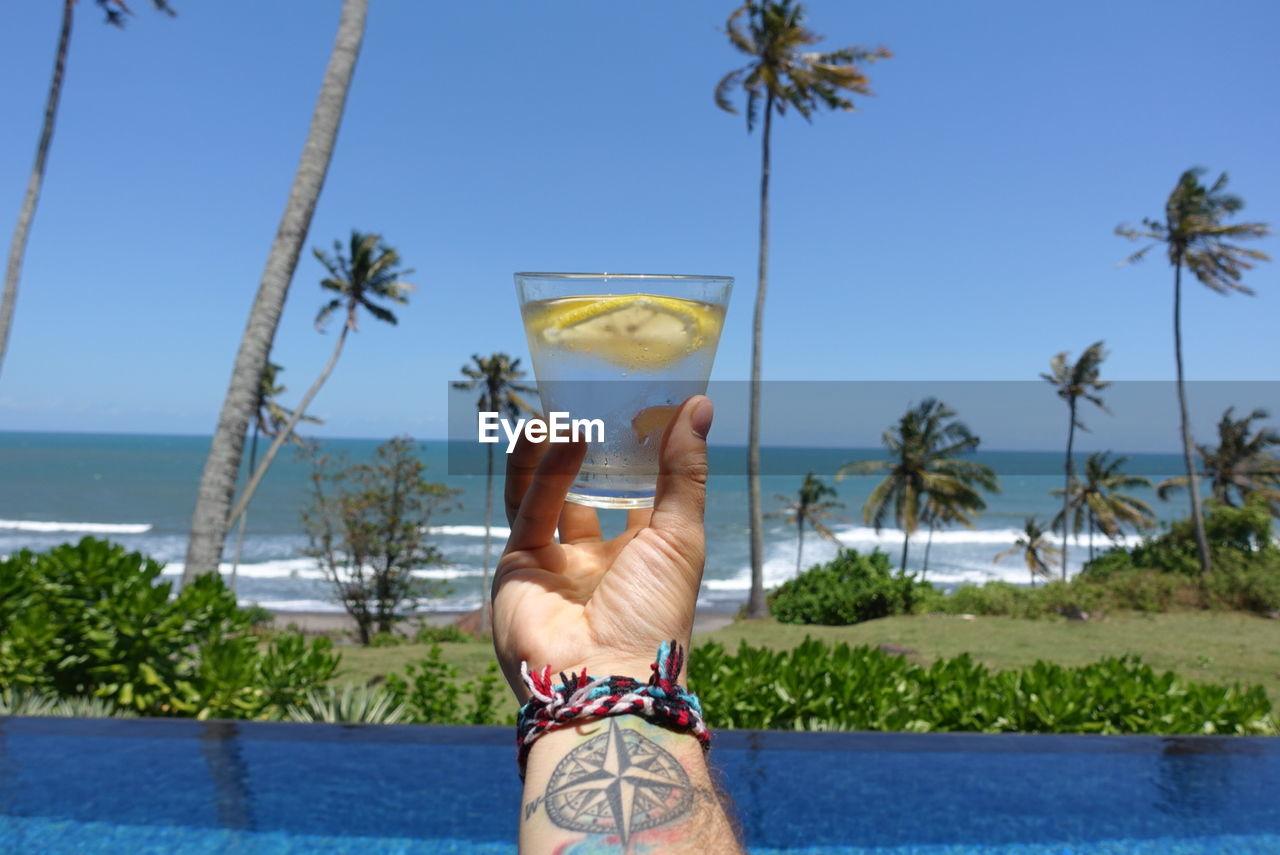 Human Hand At Beach Against Blue Sky