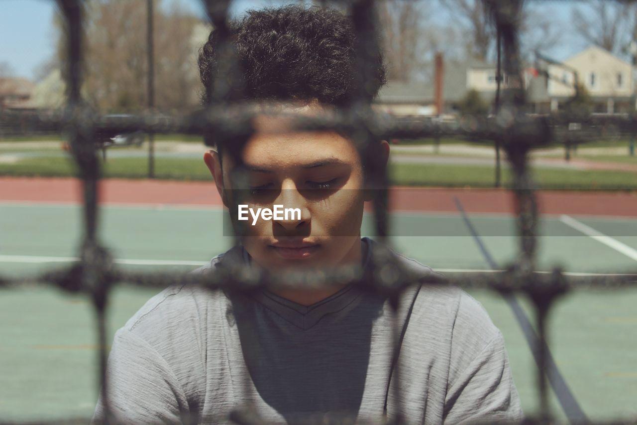 Boy Seen Through Net At Tennis Court