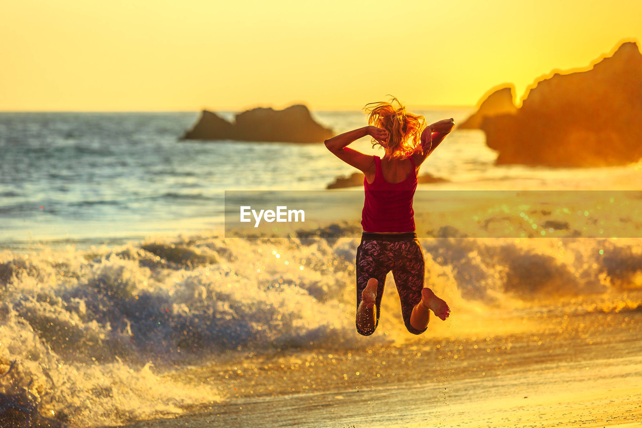 Rear view of mature woman jumping at beach against sky during sunset
