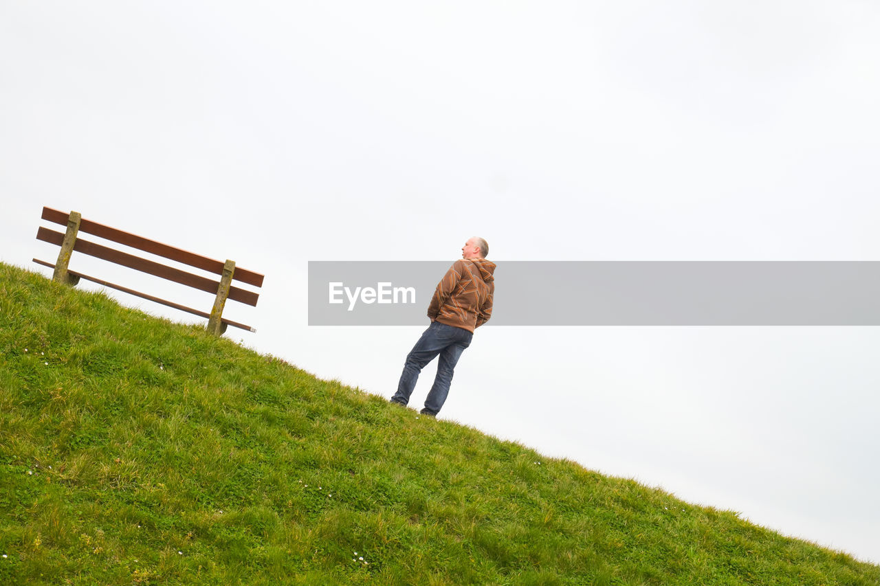 one person, sky, real people, grass, nature, plant, green color, land, lifestyles, leisure activity, full length, copy space, day, field, growth, standing, casual clothing, clear sky, rear view, outdoors, warm clothing