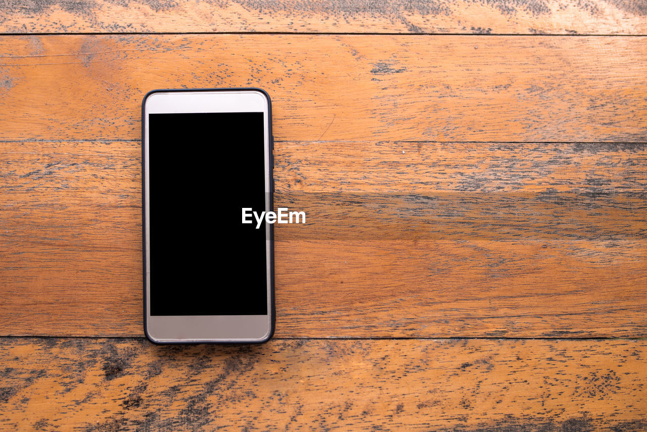 Directly above shot of smart phone on wooden table