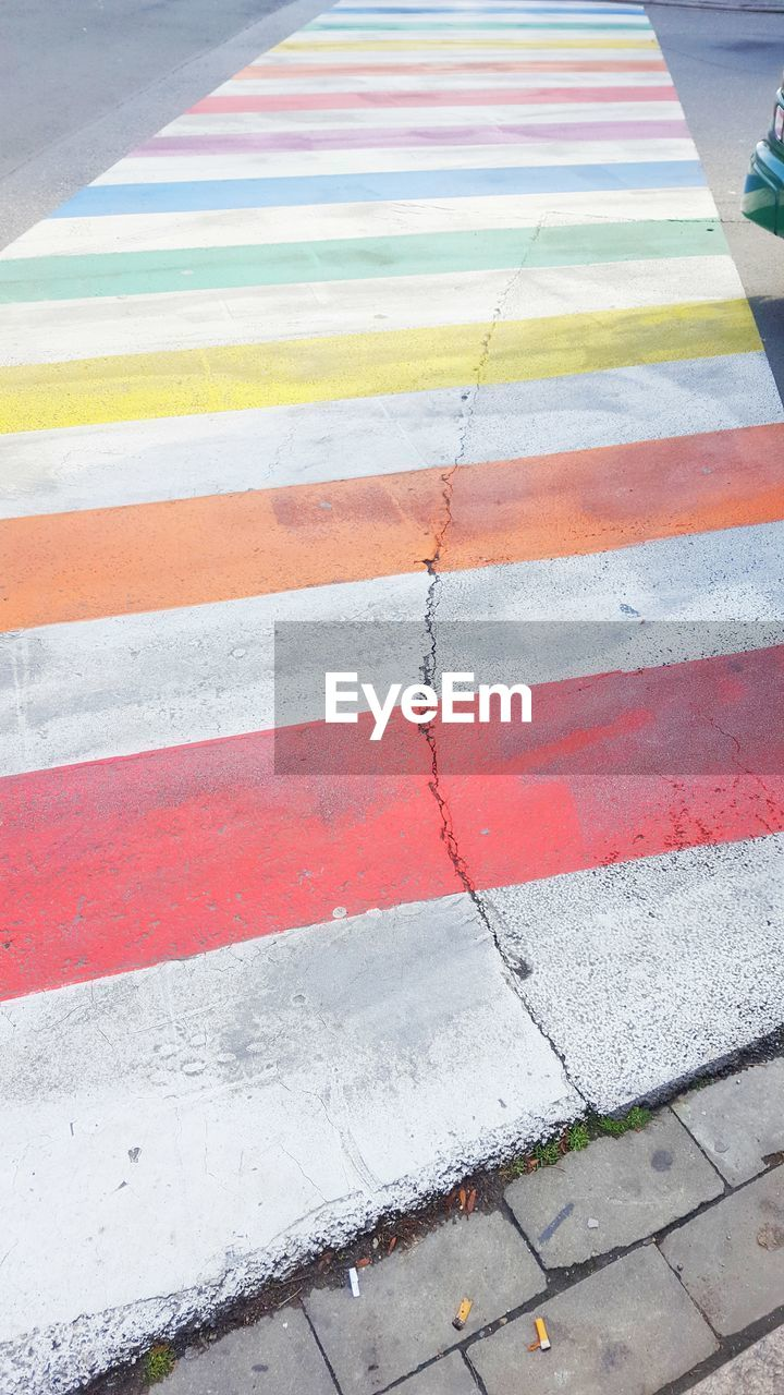 symbol, high angle view, road, marking, road marking, city, day, sign, street, no people, footpath, crosswalk, striped, transportation, outdoors, red, zebra crossing, pattern, white color, architecture, dividing line, surface level