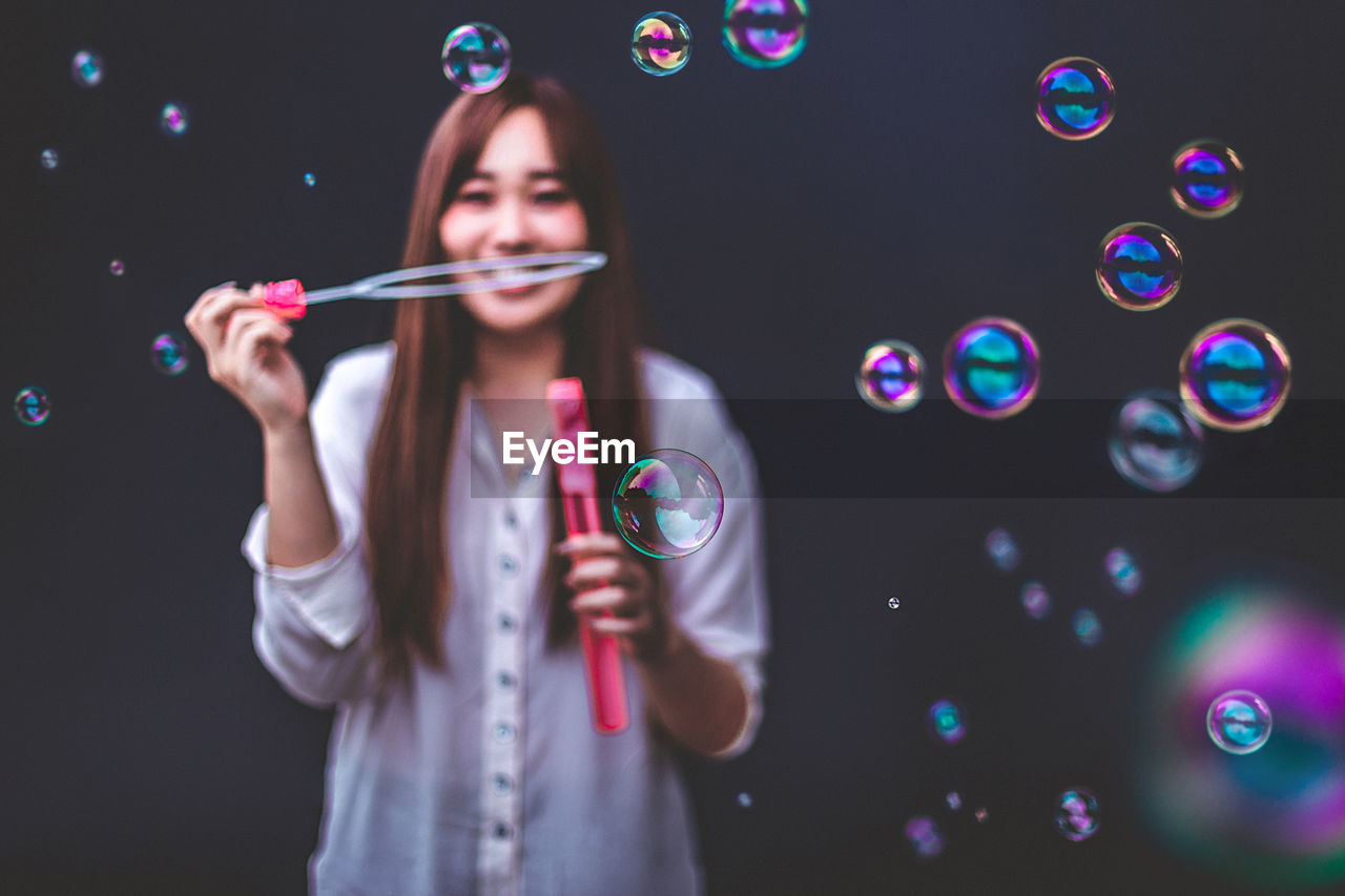 Young woman blowing bubbles while standing outdoors
