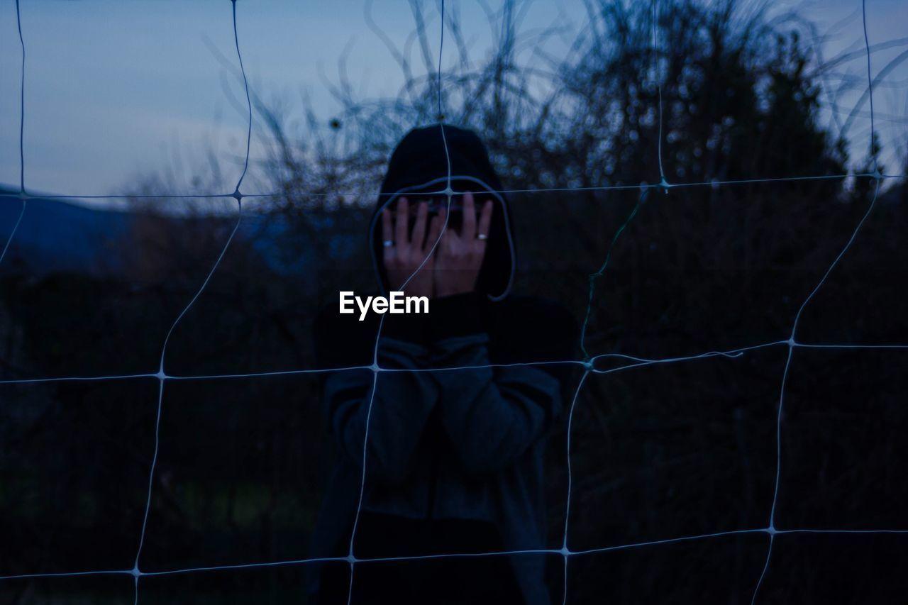 Man hiding face with hands seen through net during dusk