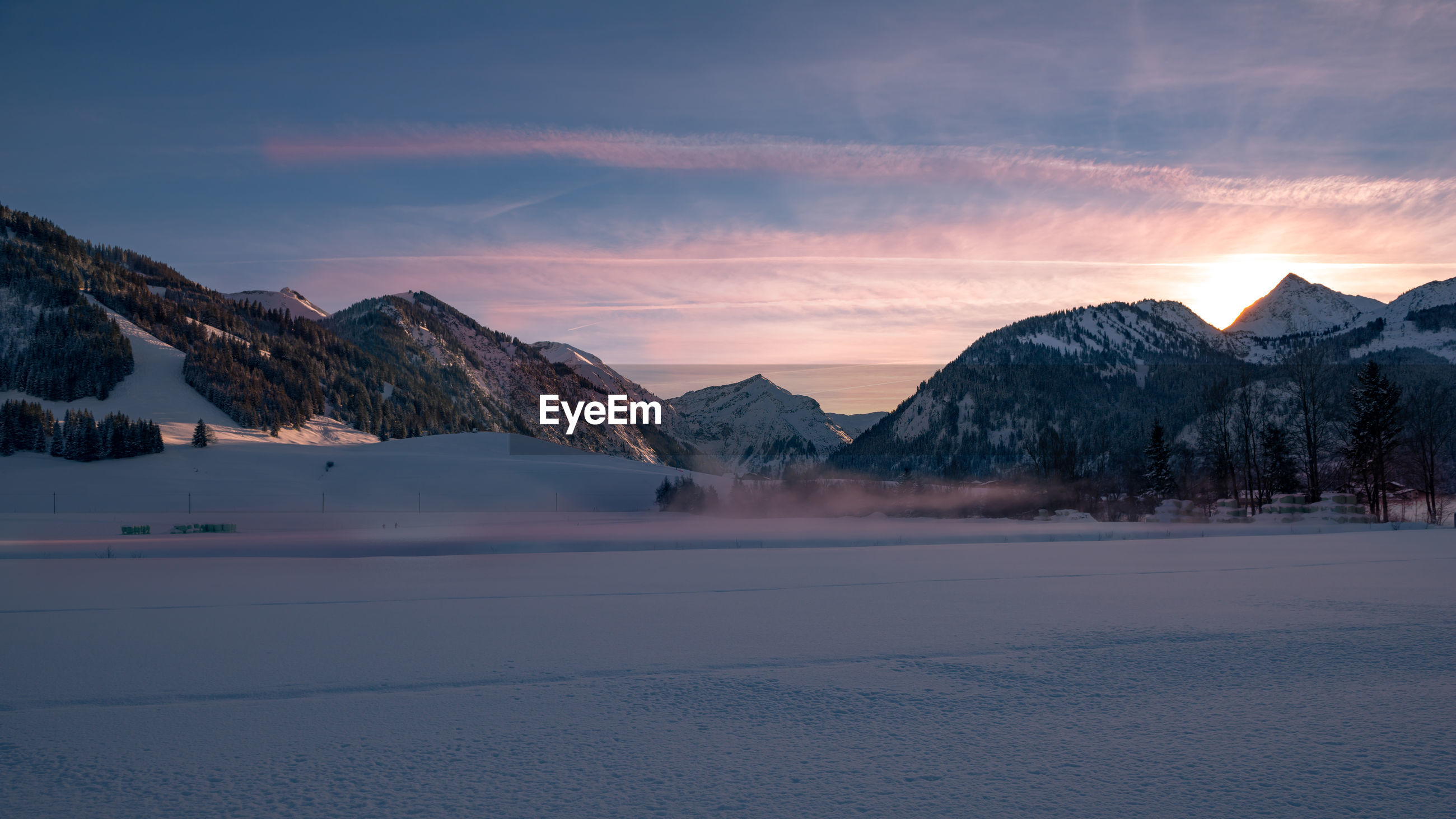 Scenic view of snow covered field against allgau alps during sunset