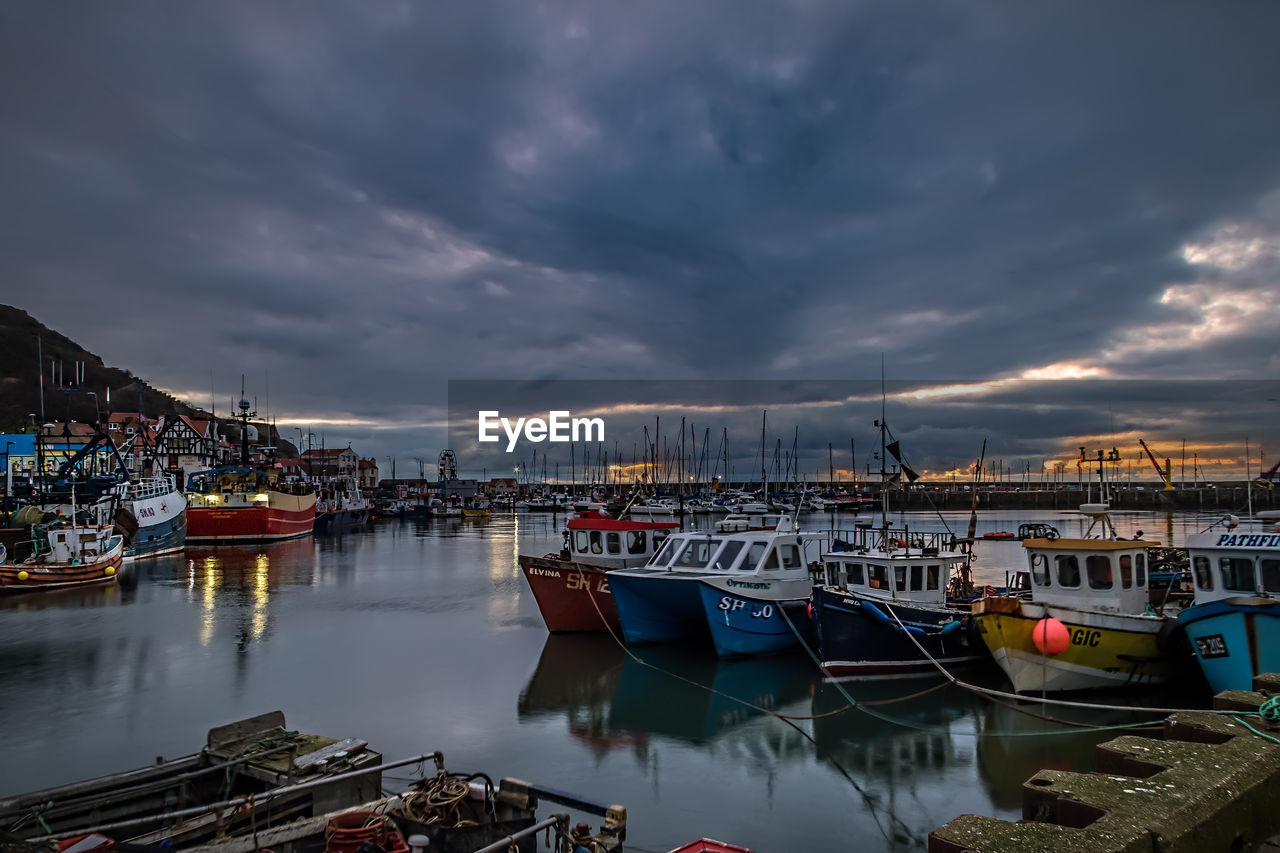 nautical vessel, moored, cloud - sky, mode of transport, sky, transportation, water, boat, reflection, built structure, harbor, sea, no people, outdoors, sunset, architecture, building exterior, nature, tranquility, travel destinations, mast, scenics, sailboat, day, yacht, beauty in nature, city