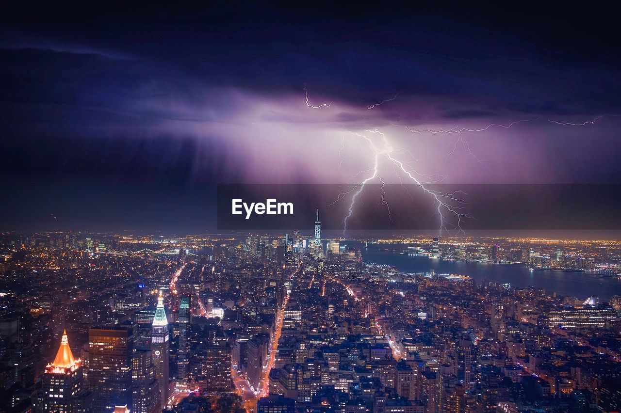 cityscape, lightning, illuminated, power in nature, night, city, thunderstorm, forked lightning, architecture, building exterior, sky, no people, city life, storm, outdoors, built structure, electricity, skyscraper, urban skyline, storm cloud, nature