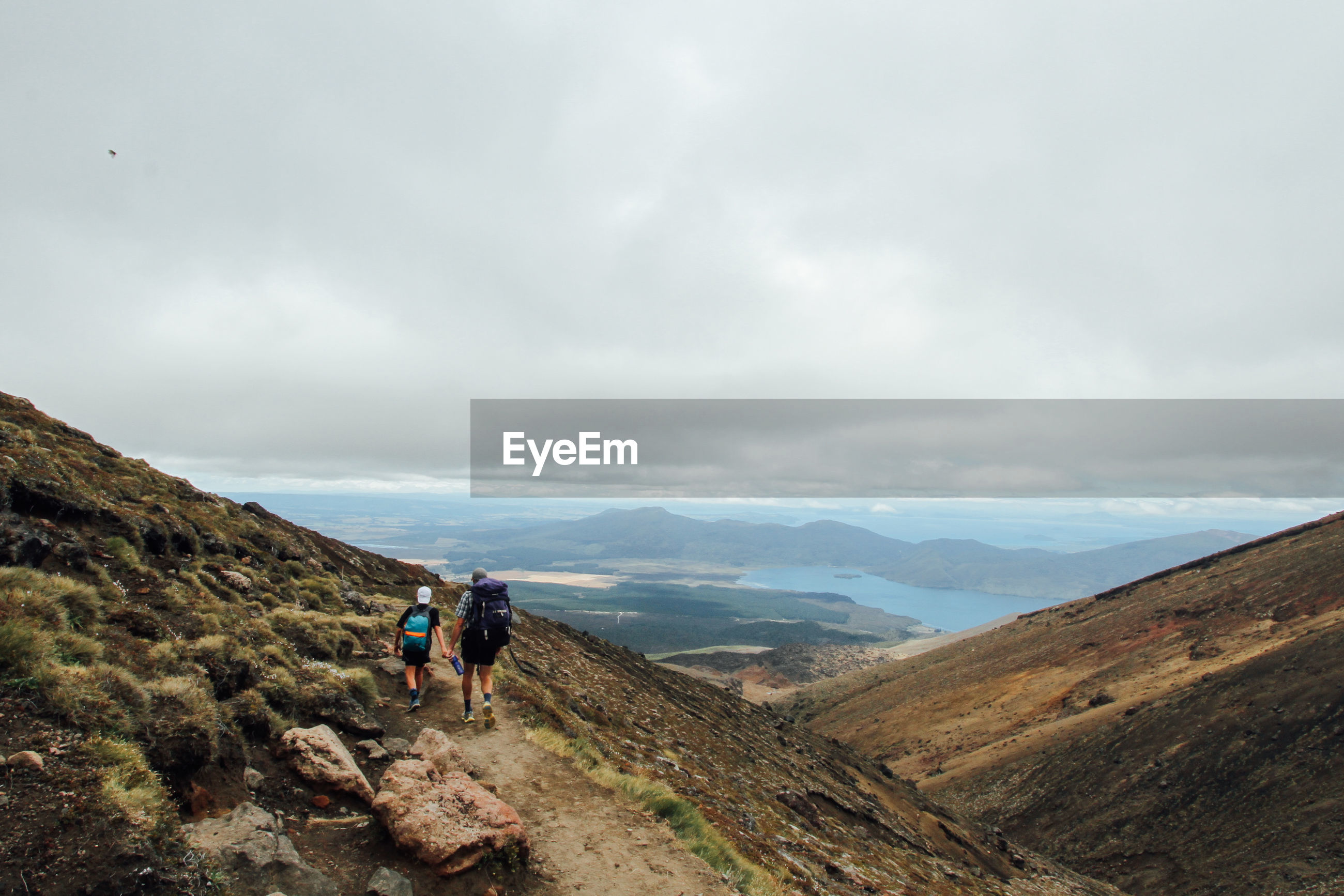 Rear view of man with son hiking on mountain against cloudy sky