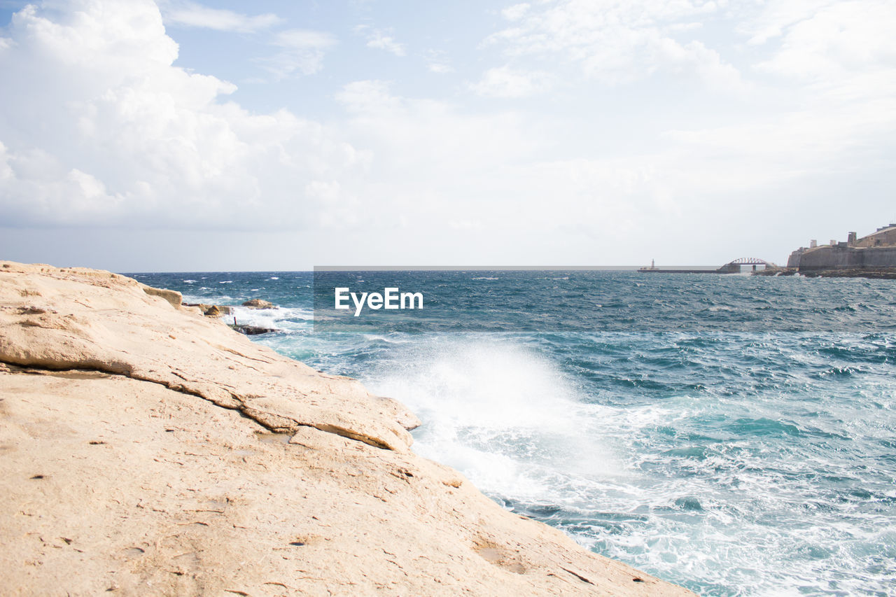 sea, water, sky, beauty in nature, horizon, horizon over water, scenics - nature, land, motion, wave, rock, sport, beach, cloud - sky, nature, day, rock - object, aquatic sport, no people, outdoors, power in nature, breaking