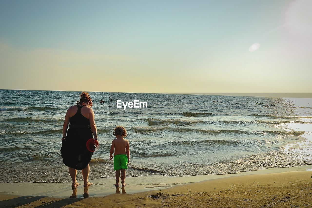 Rear view of mother and son standing on beach against sky