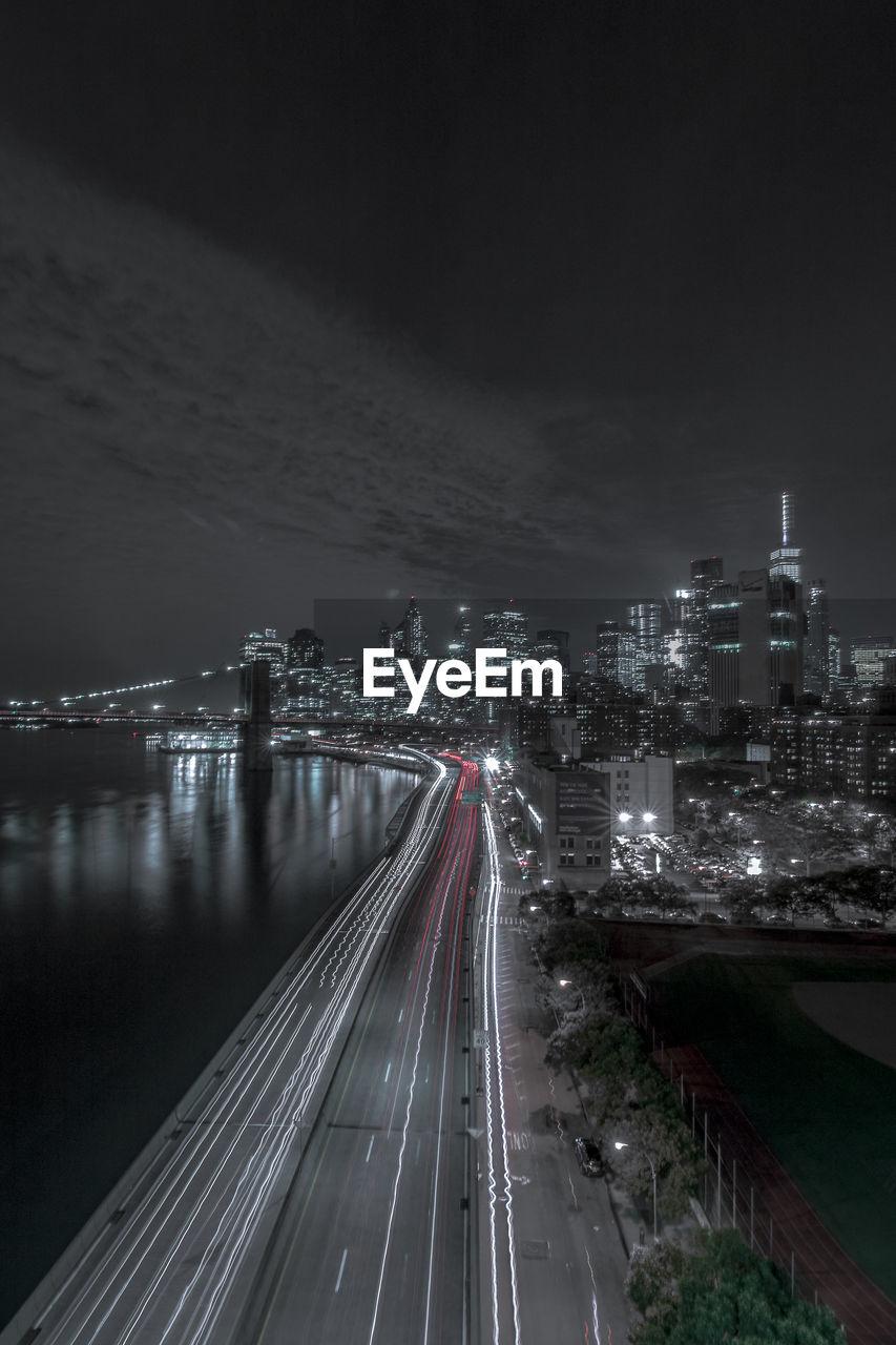 Light Trails On Road By Illuminated Urban Skyline