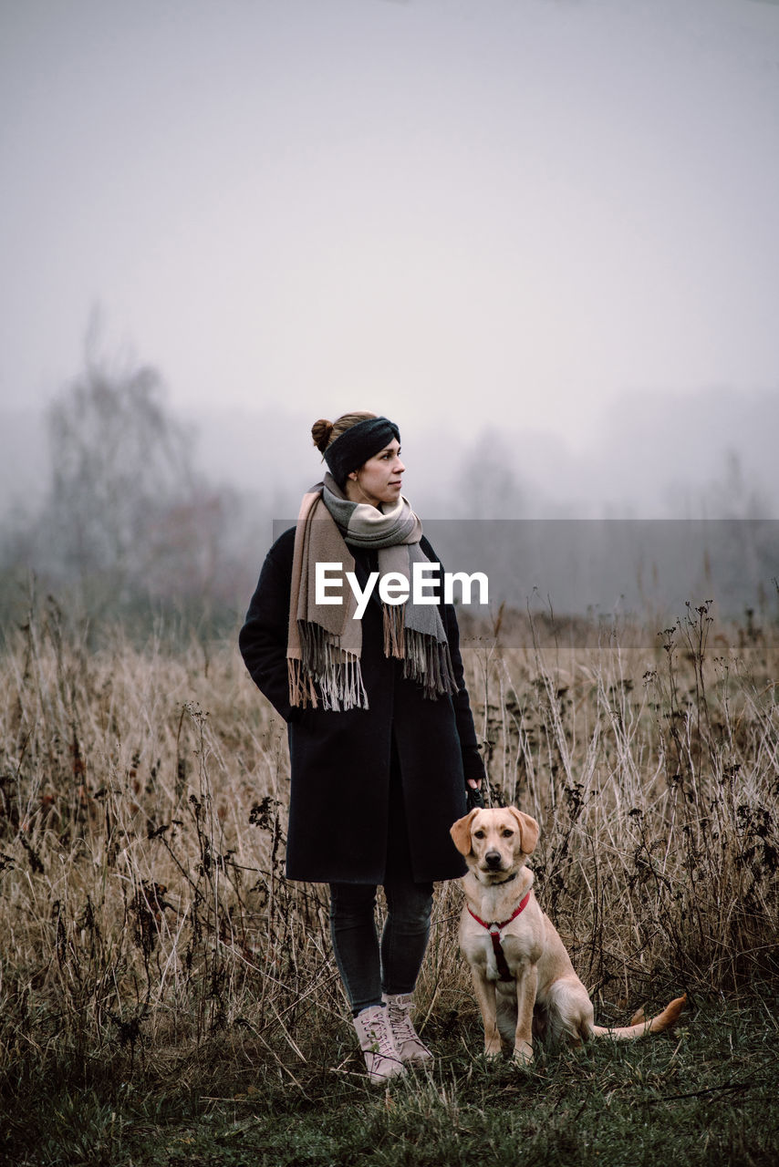 Full Length Of Woman With Dog Standing On Field During Winter