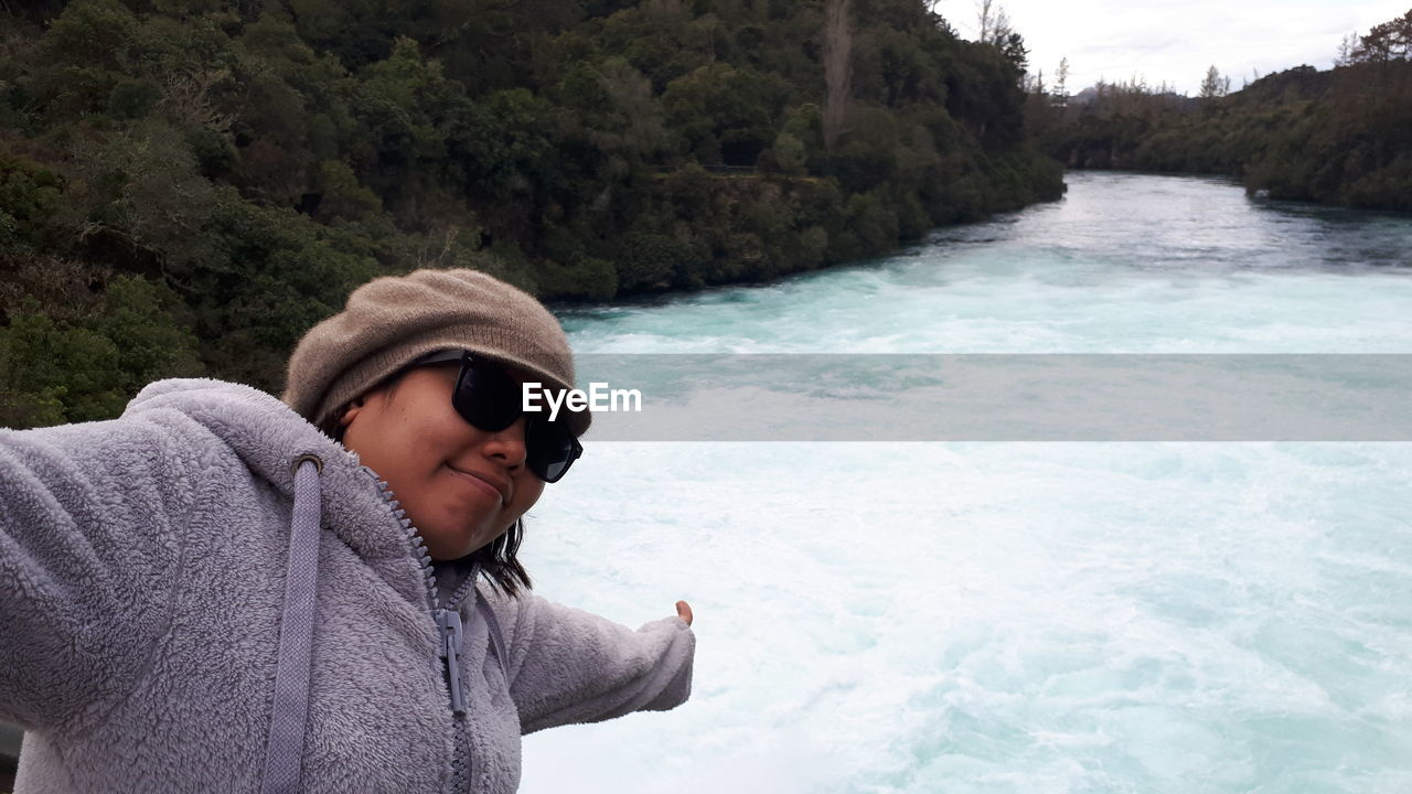 Smiling Woman With Arms Outstretched At Huka Falls